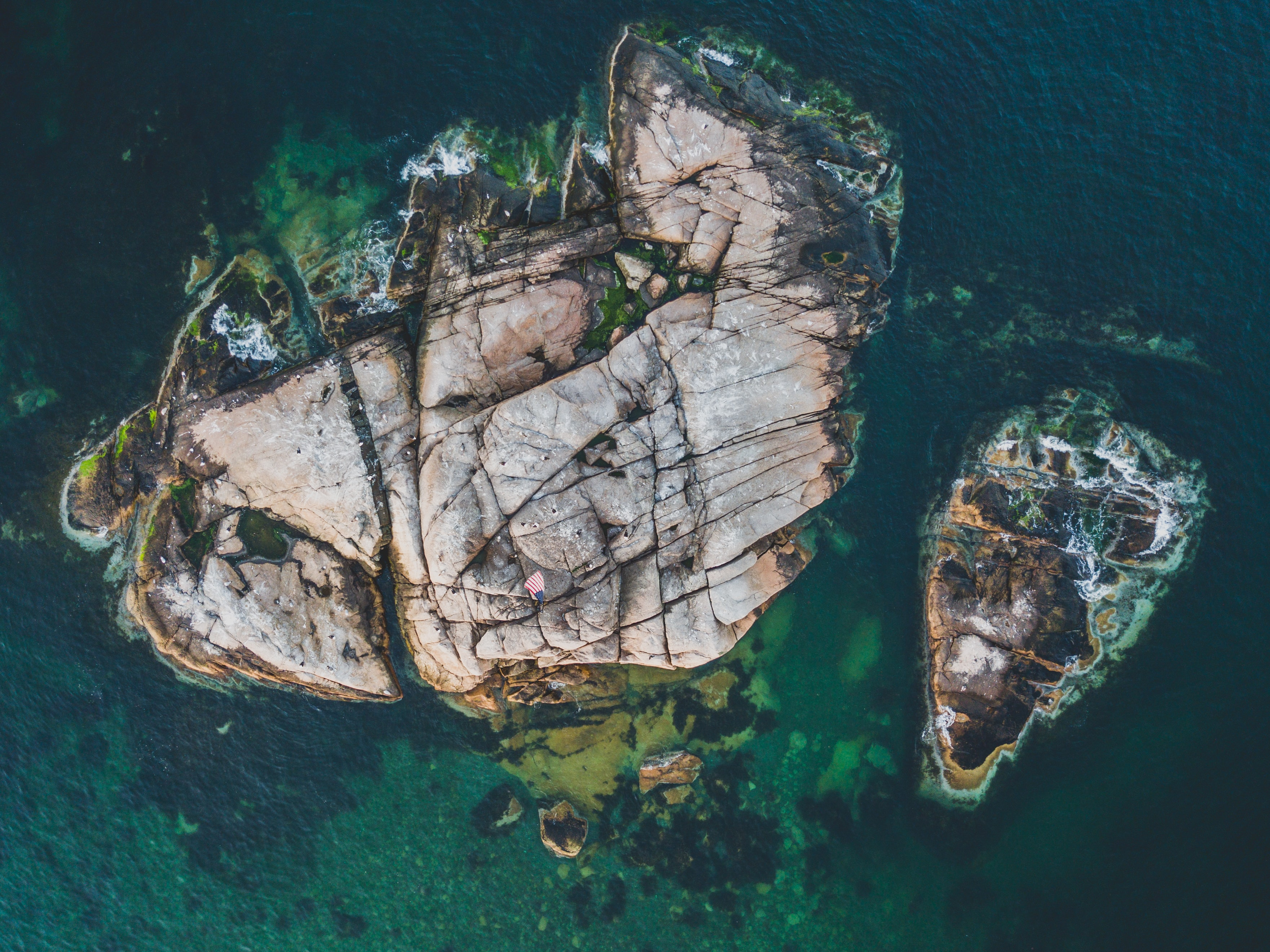 brown rock formation on water aerial photogrpahy