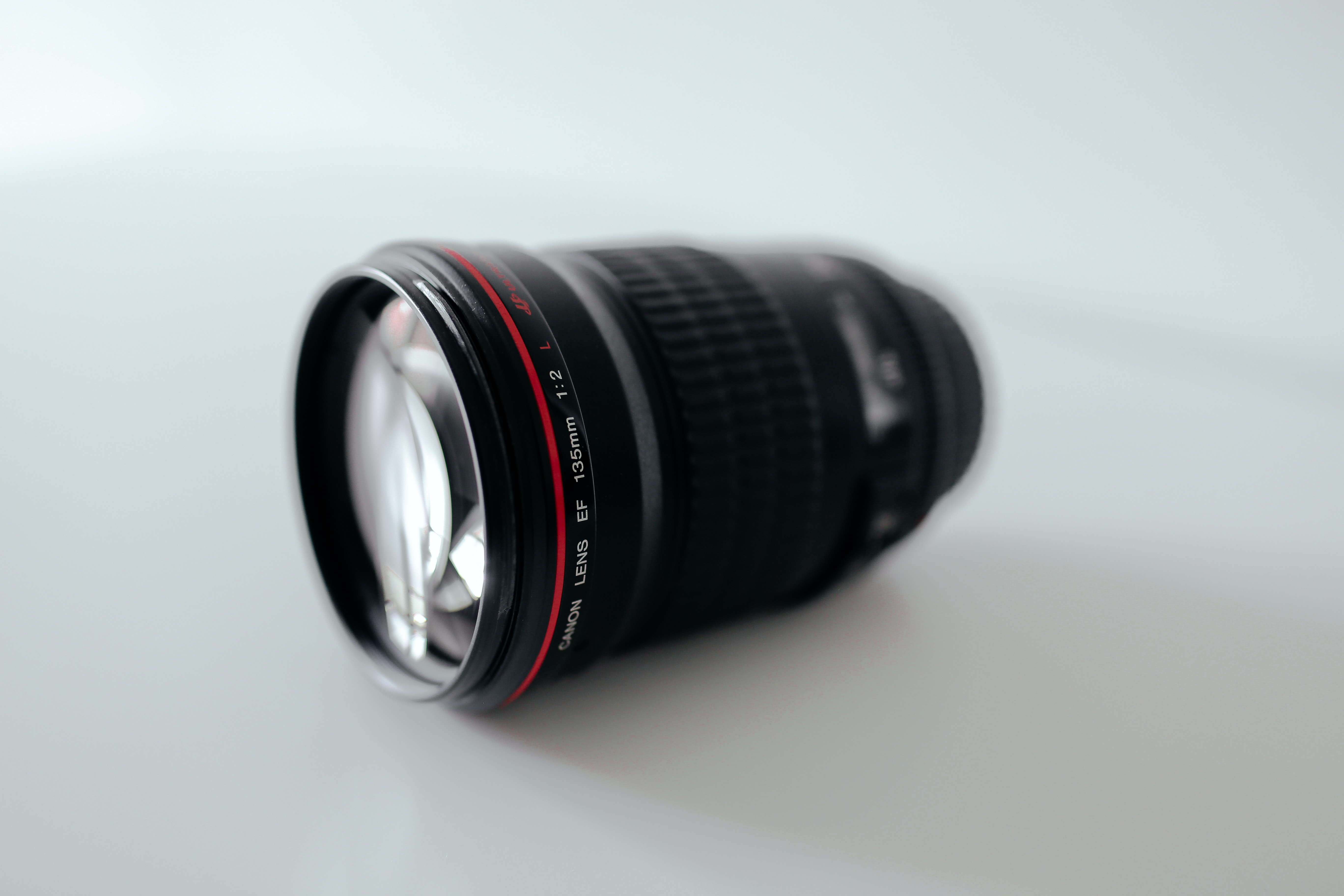closeup photography of black camera lens on white surface