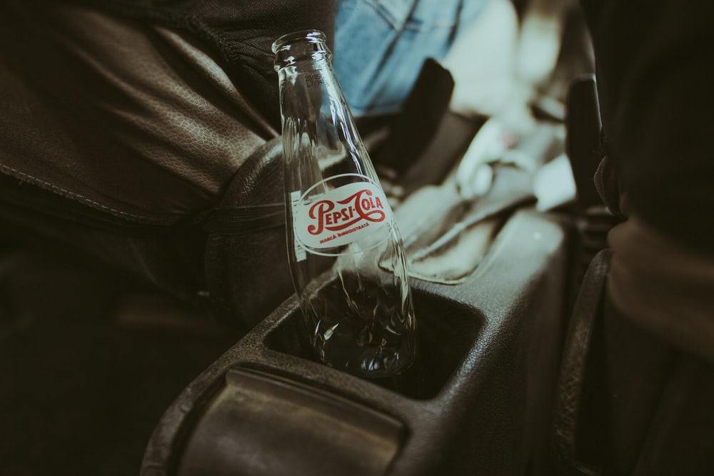 coca cola glass bottle on black textile