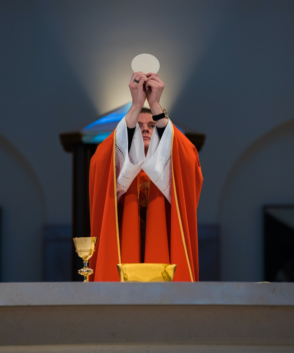A priest in a red robe offering communion in front of an altar in Kingwood