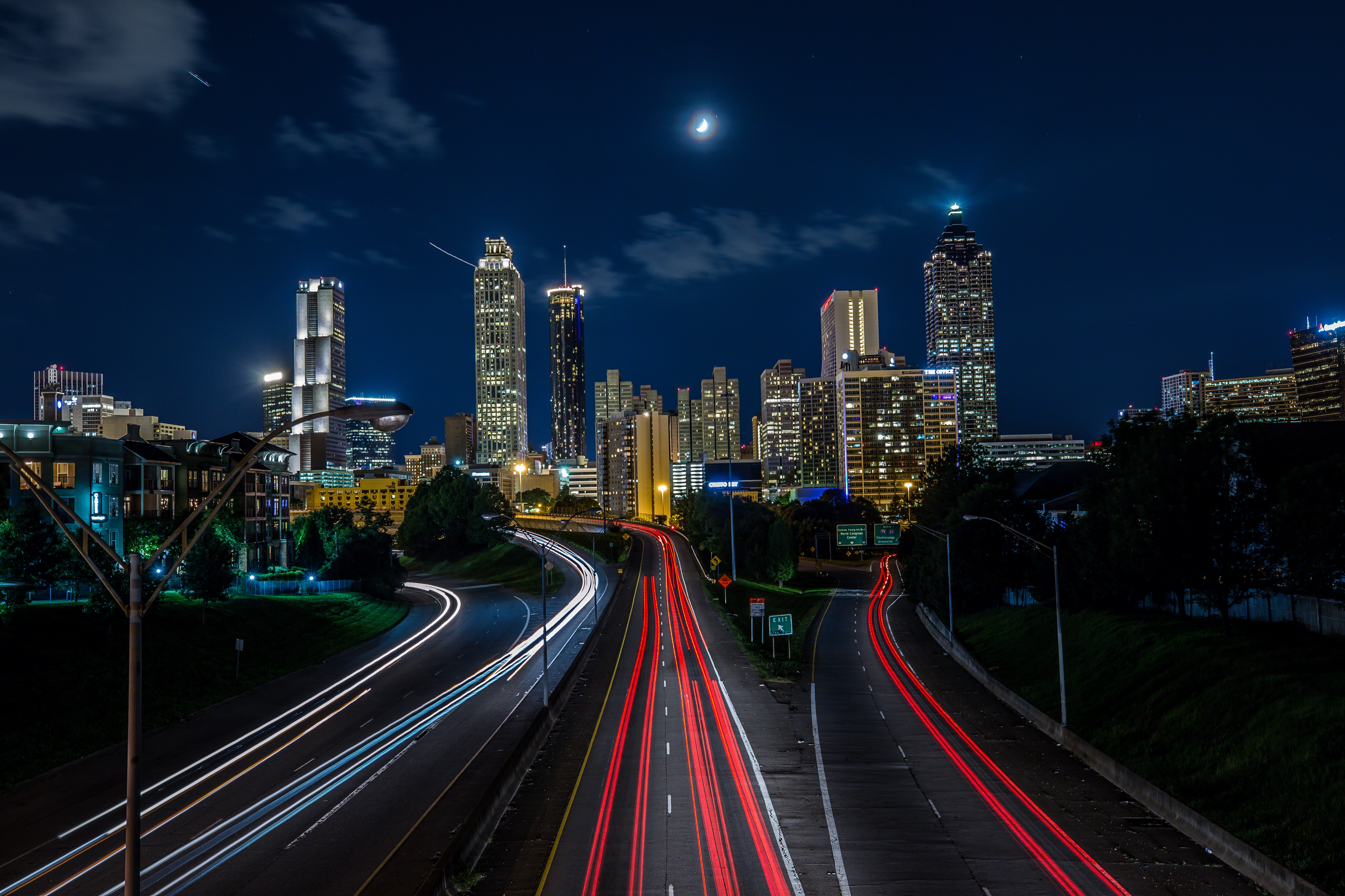 Long exposure shot of Jackson Street Bridge and surrounding skyscrapers over which the half moon shines