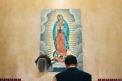 後光が出ている聖母の絵画に祈りを捧げる新郎新婦の様子