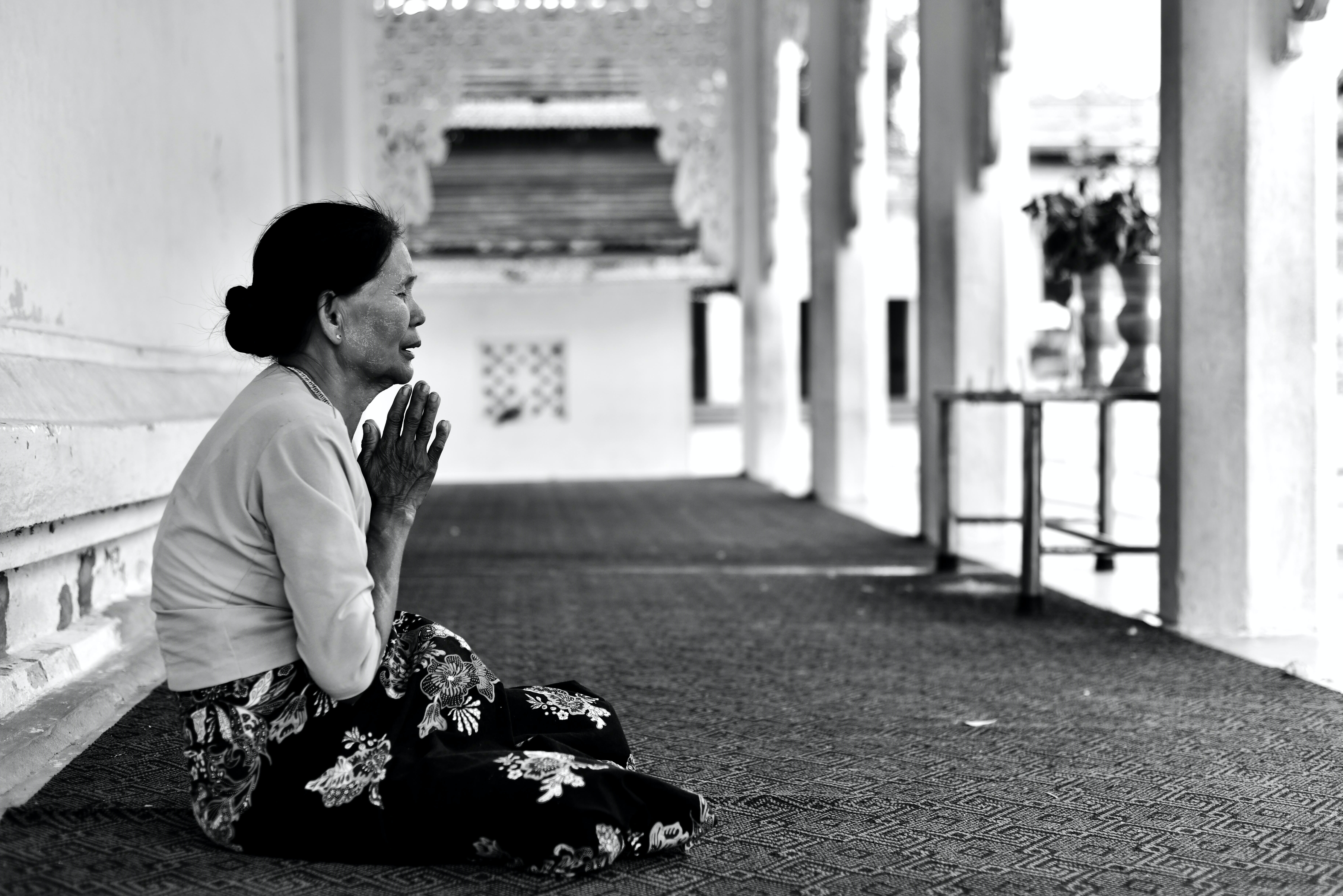 A woman sits on a mat on the ground, praying, in the Mandalay Region