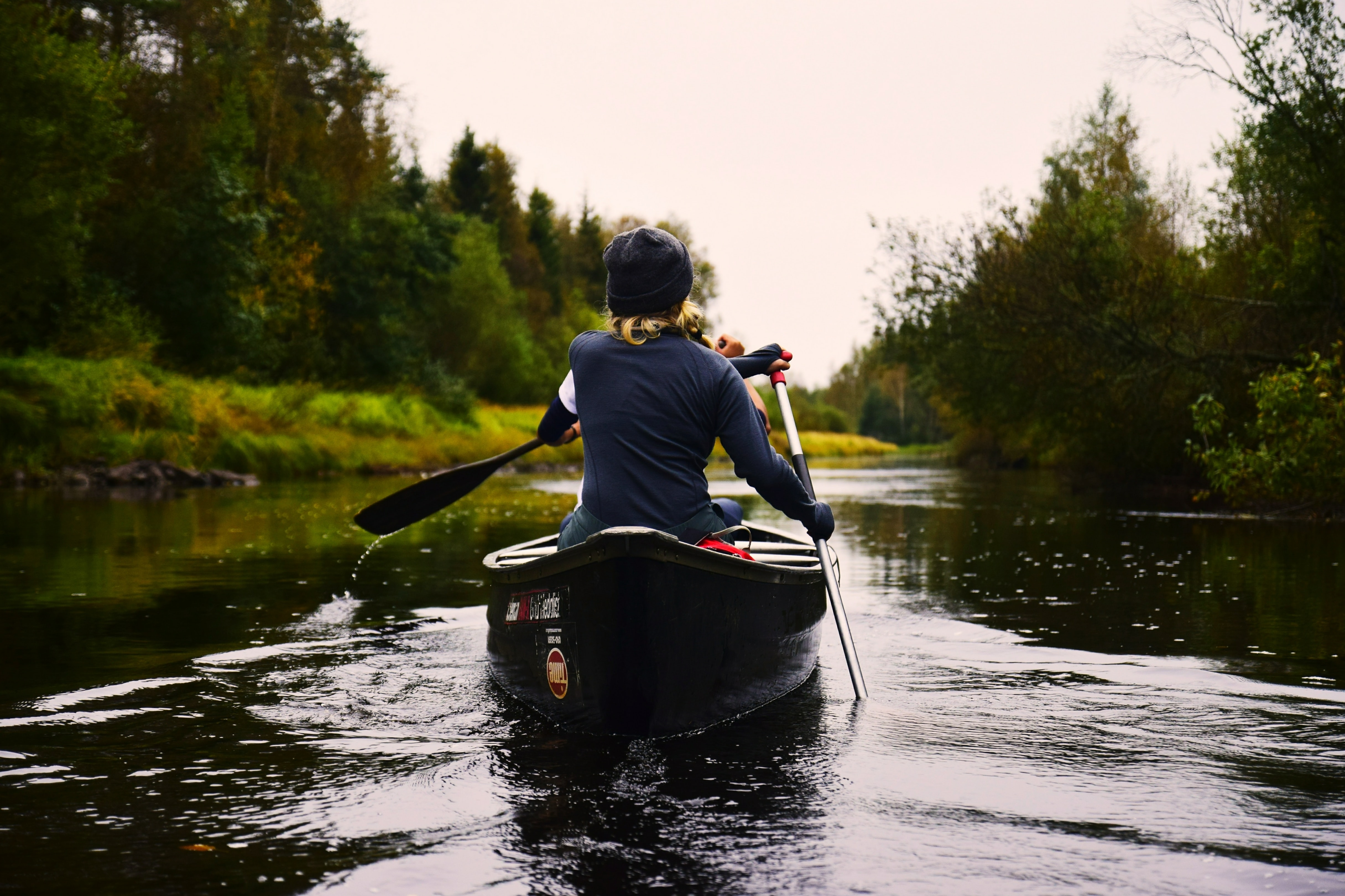 A woman rowing a canoe down a river with green trees along the sides