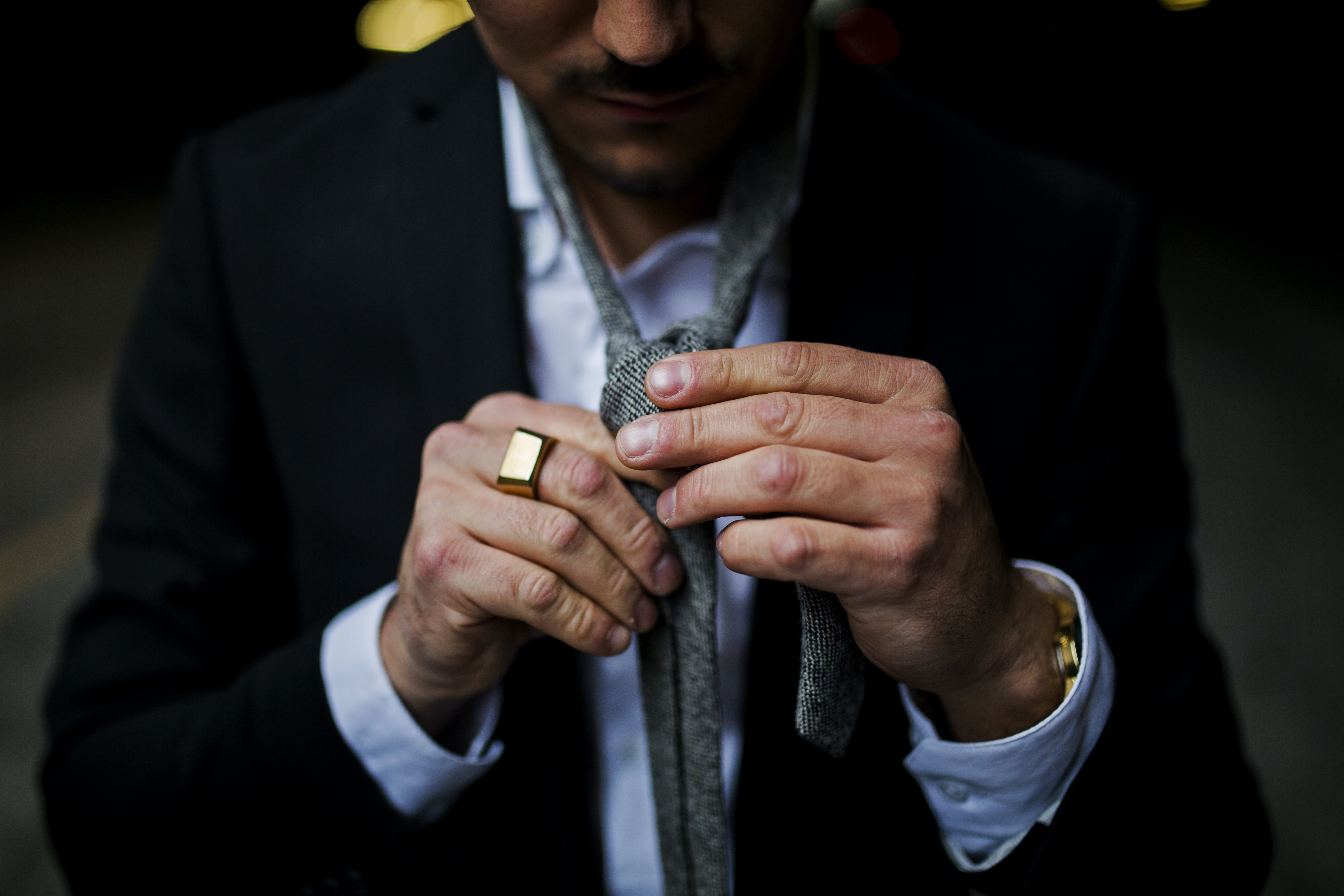 A man in a suit jacket tying his tie