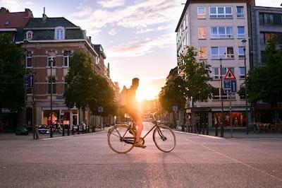 man riding bicycle on road during daytime belgium teams background