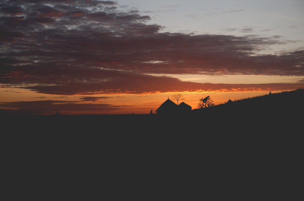 photo of silhouette of house during sunset