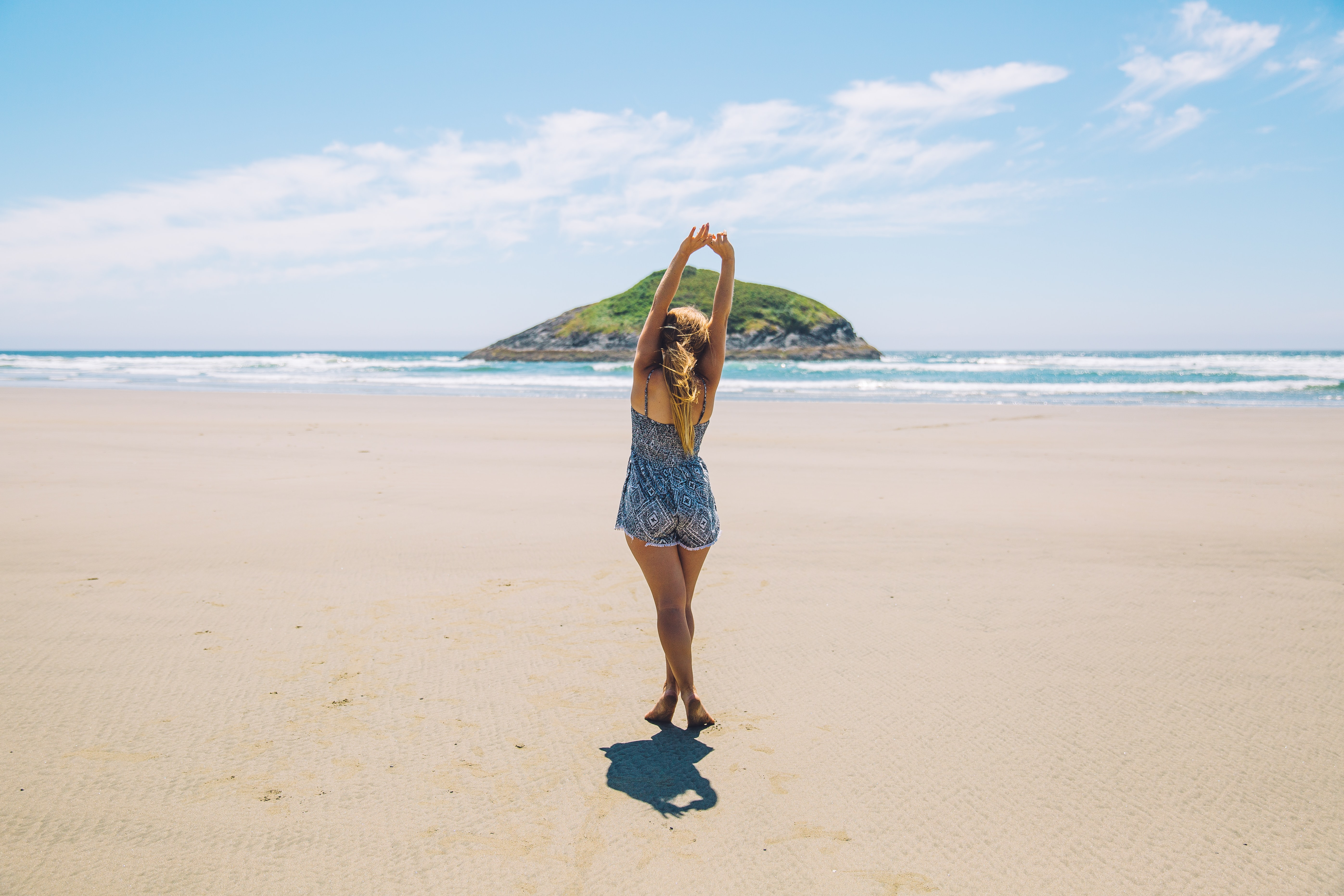 Young woman stretching on a sand beach with an island in the background in Tofino
