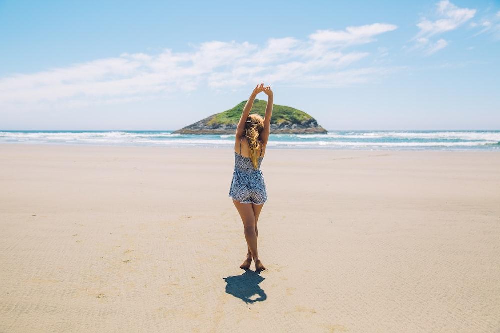 woman on seashore near island under blue sky