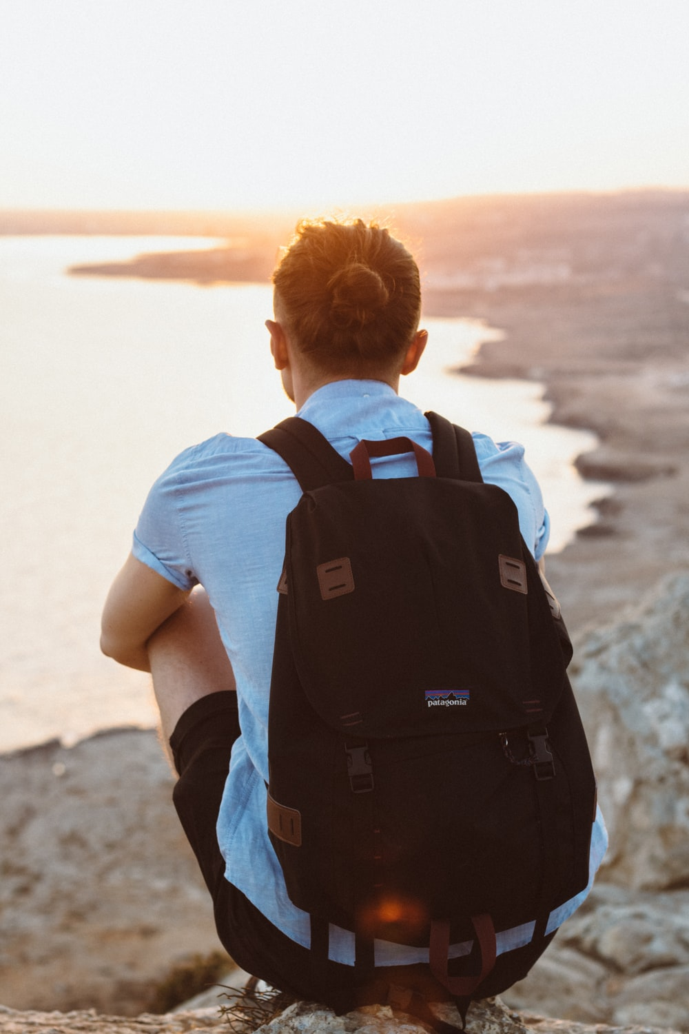 person in black knapsack sitting on cliff