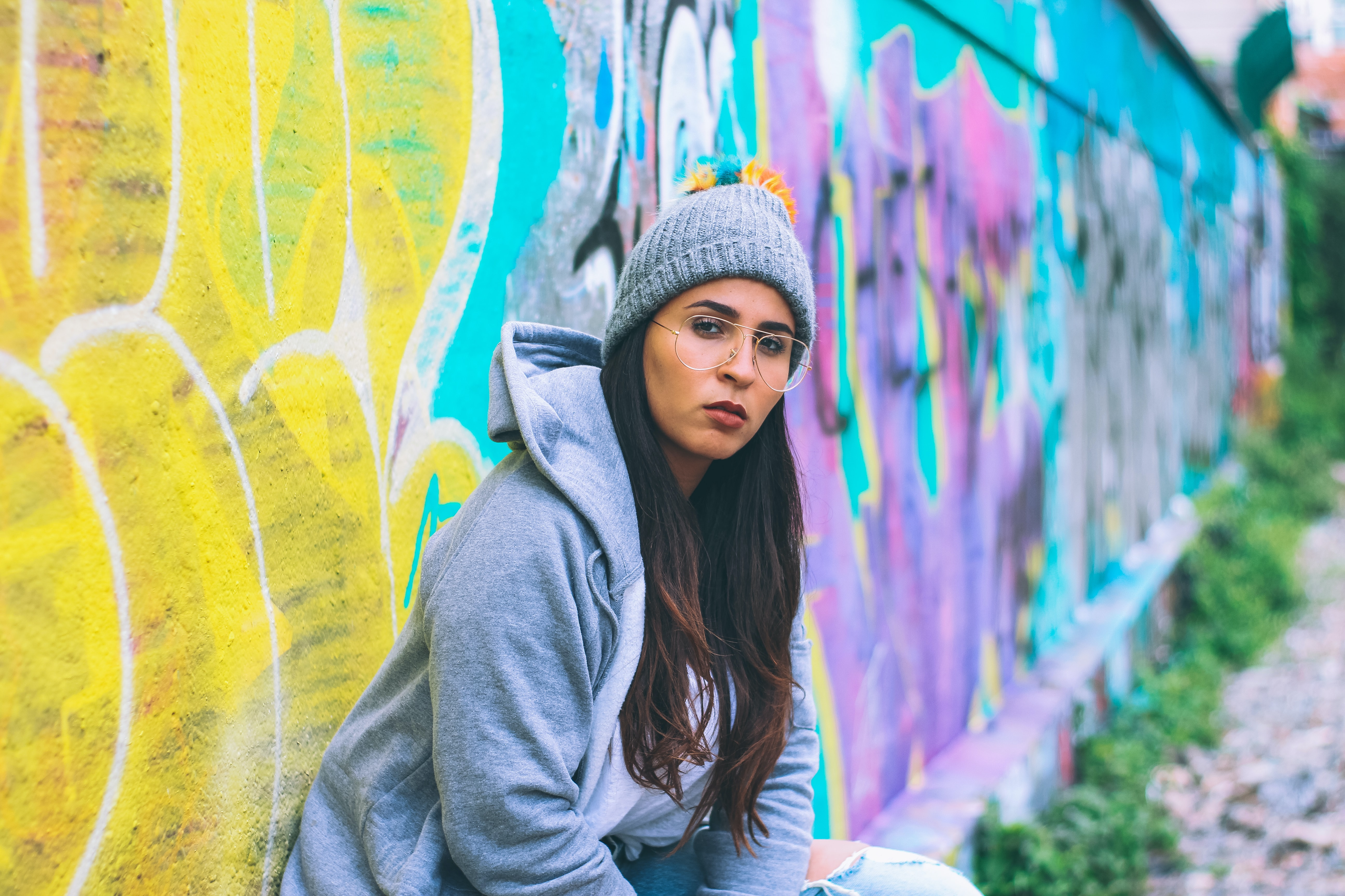 Fashionable urban female with glasses and beanie hat sitting in front of colorful graffiti, Paris