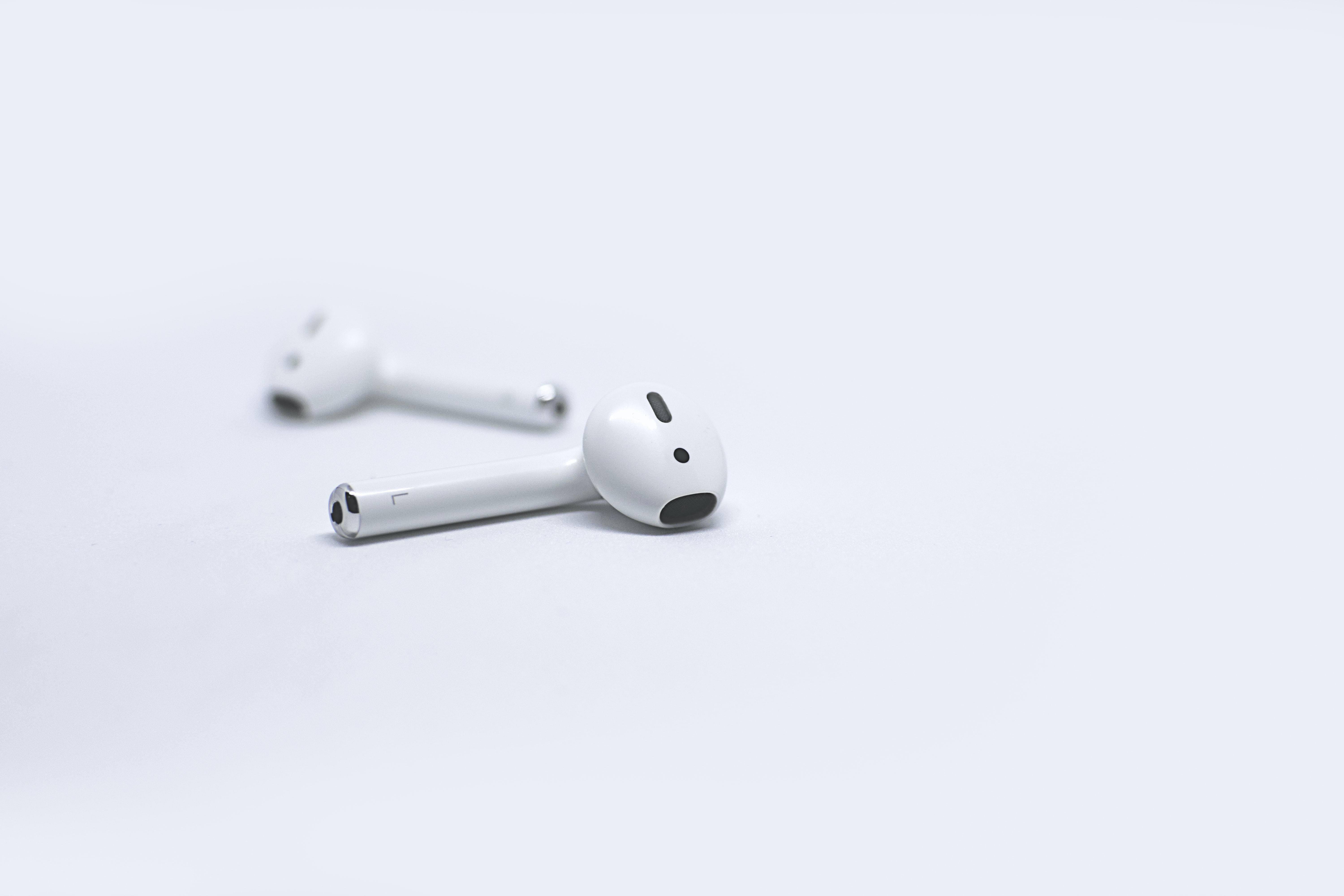 White iPhone wireless earbuds on white surface