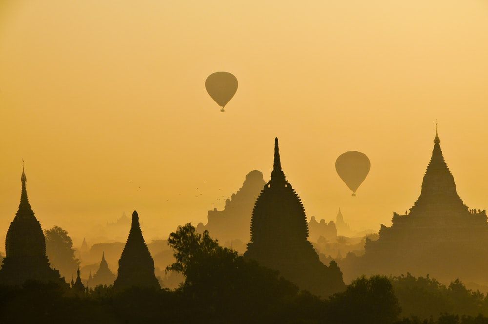 silhouette of two hot air balloons near temple