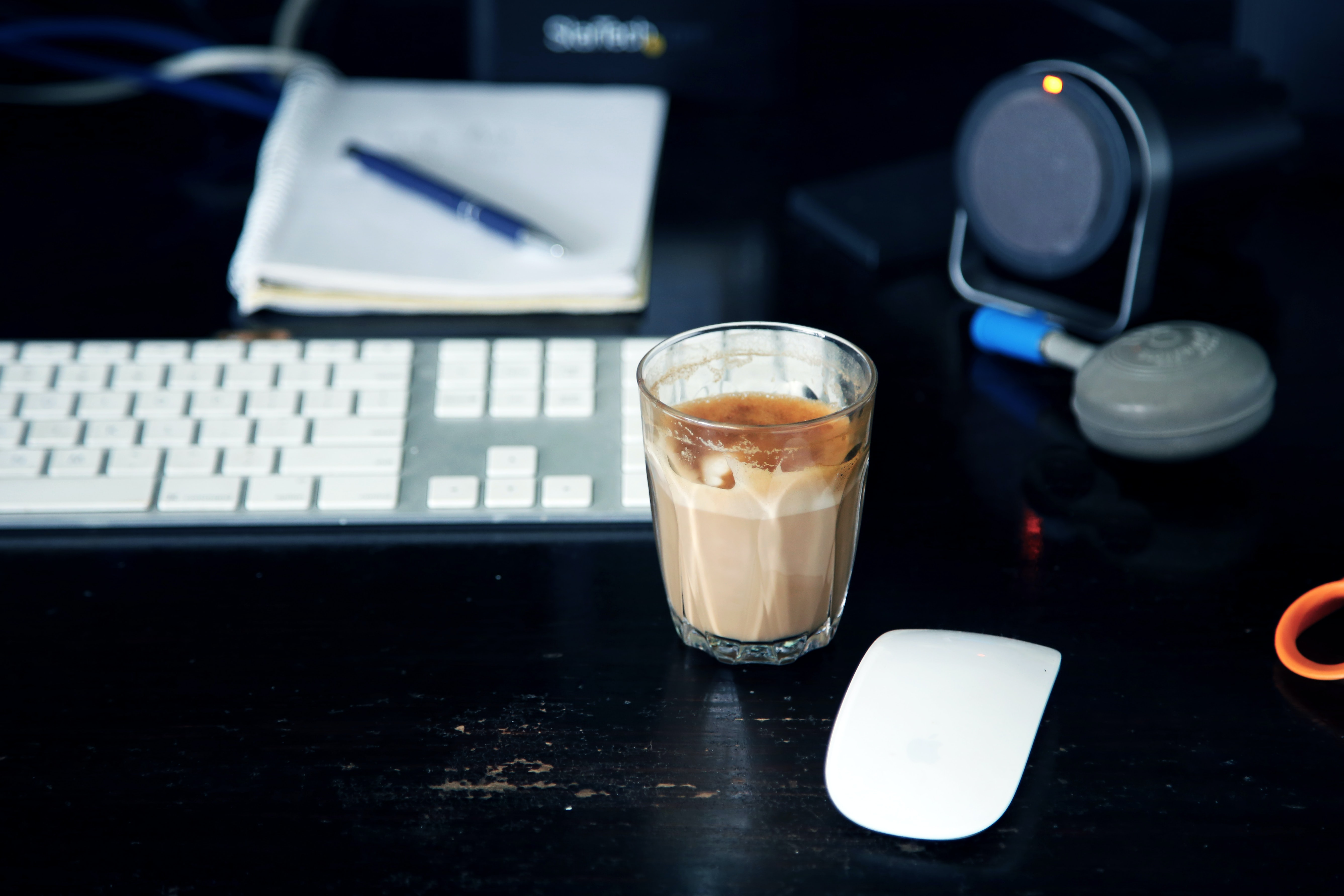 A glass of latte on a work desk.