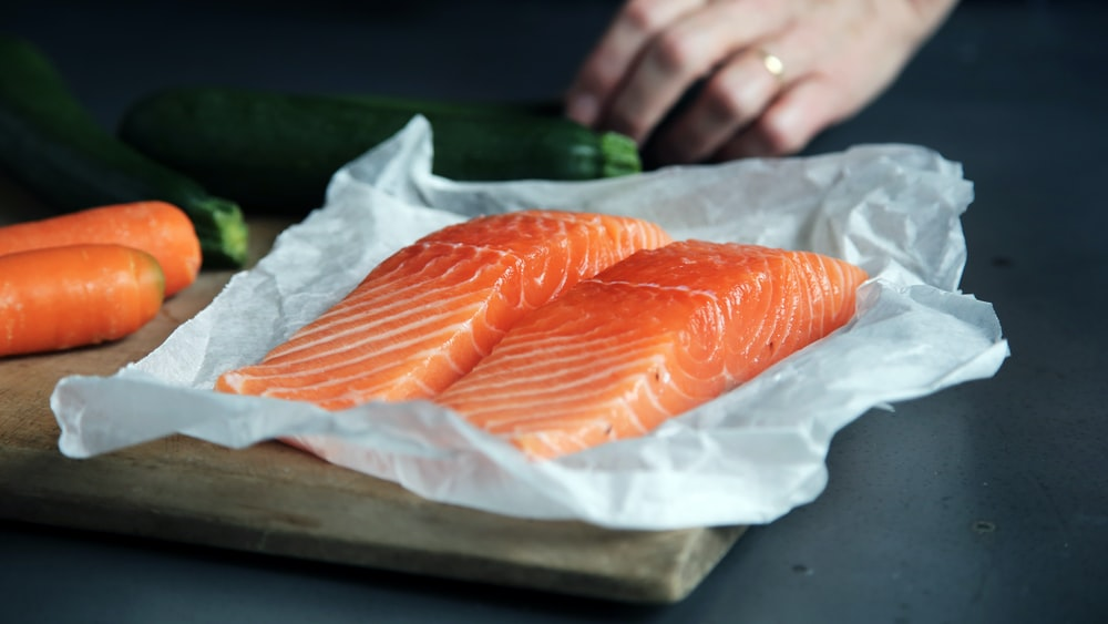 raw fish meat on brown chopping board