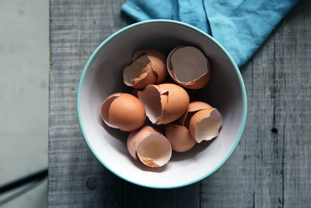 brown eggshells in round white ceramic bowl on gray wooden board top-view photography
