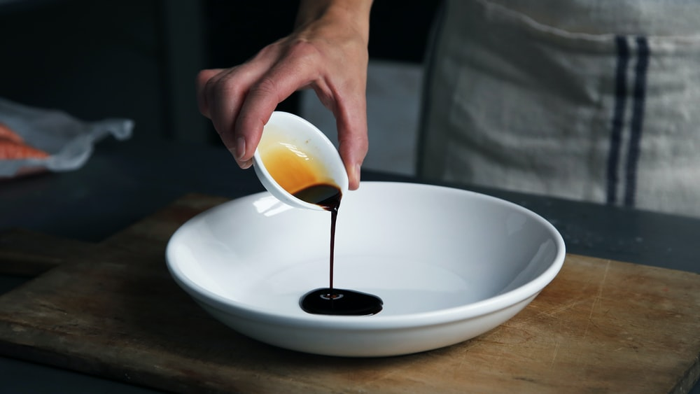 A chef pouring balsamic vinegar on a large bowl plate.