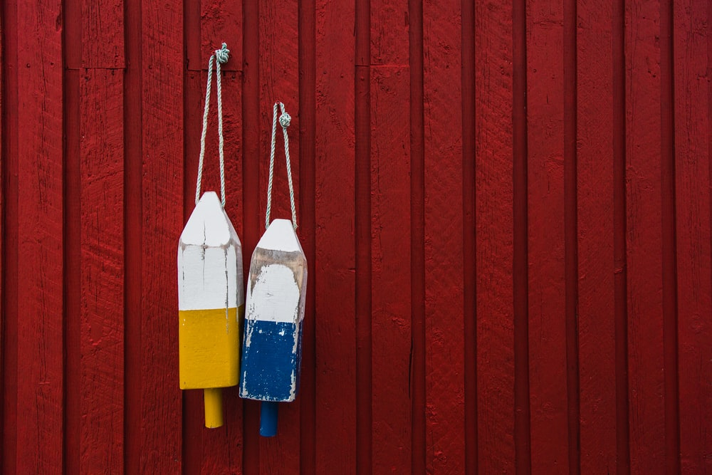 two yellow and blue hanging decors behind red wall