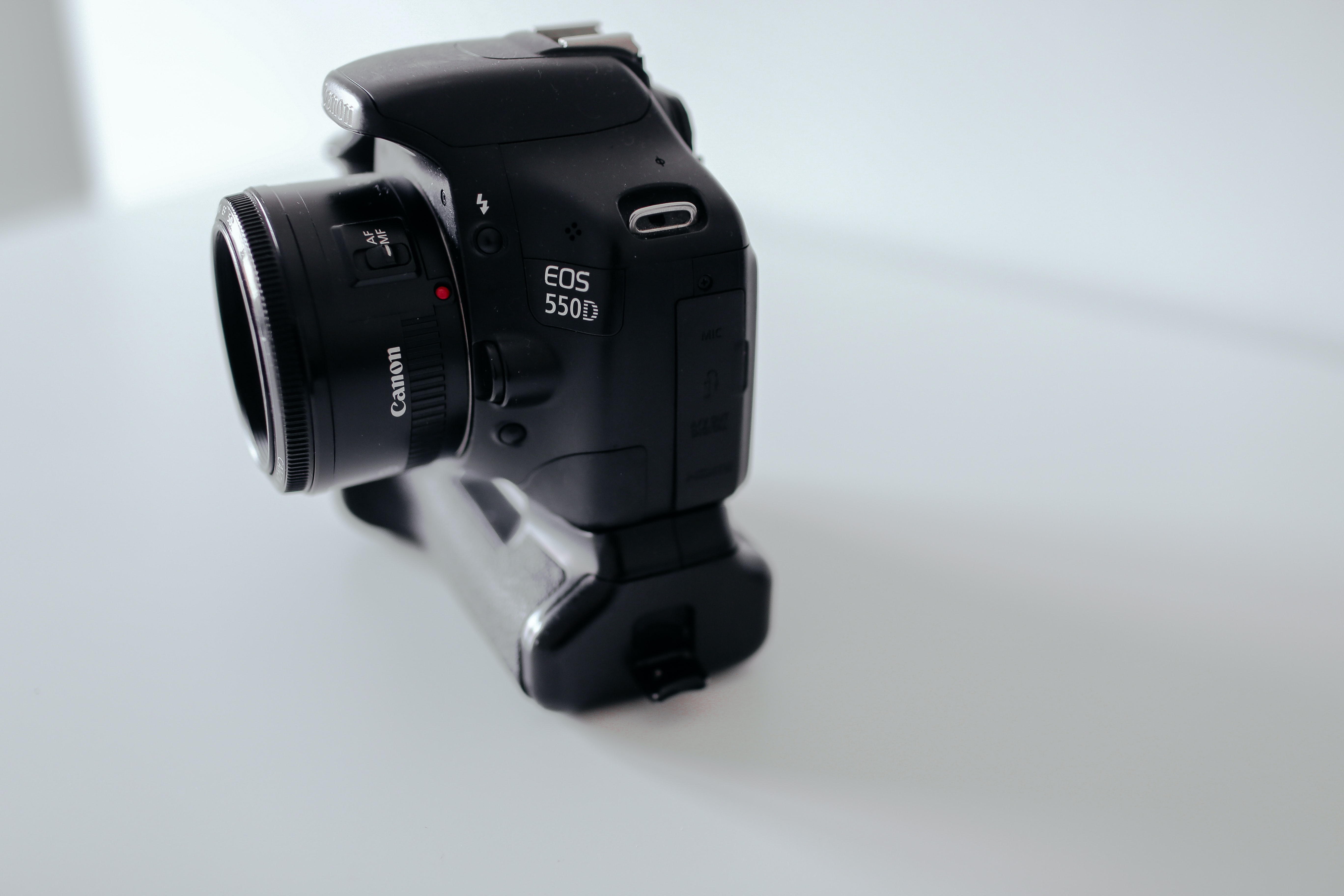 Canon EOS 550D Camera with lens and a battery pack on a white surface