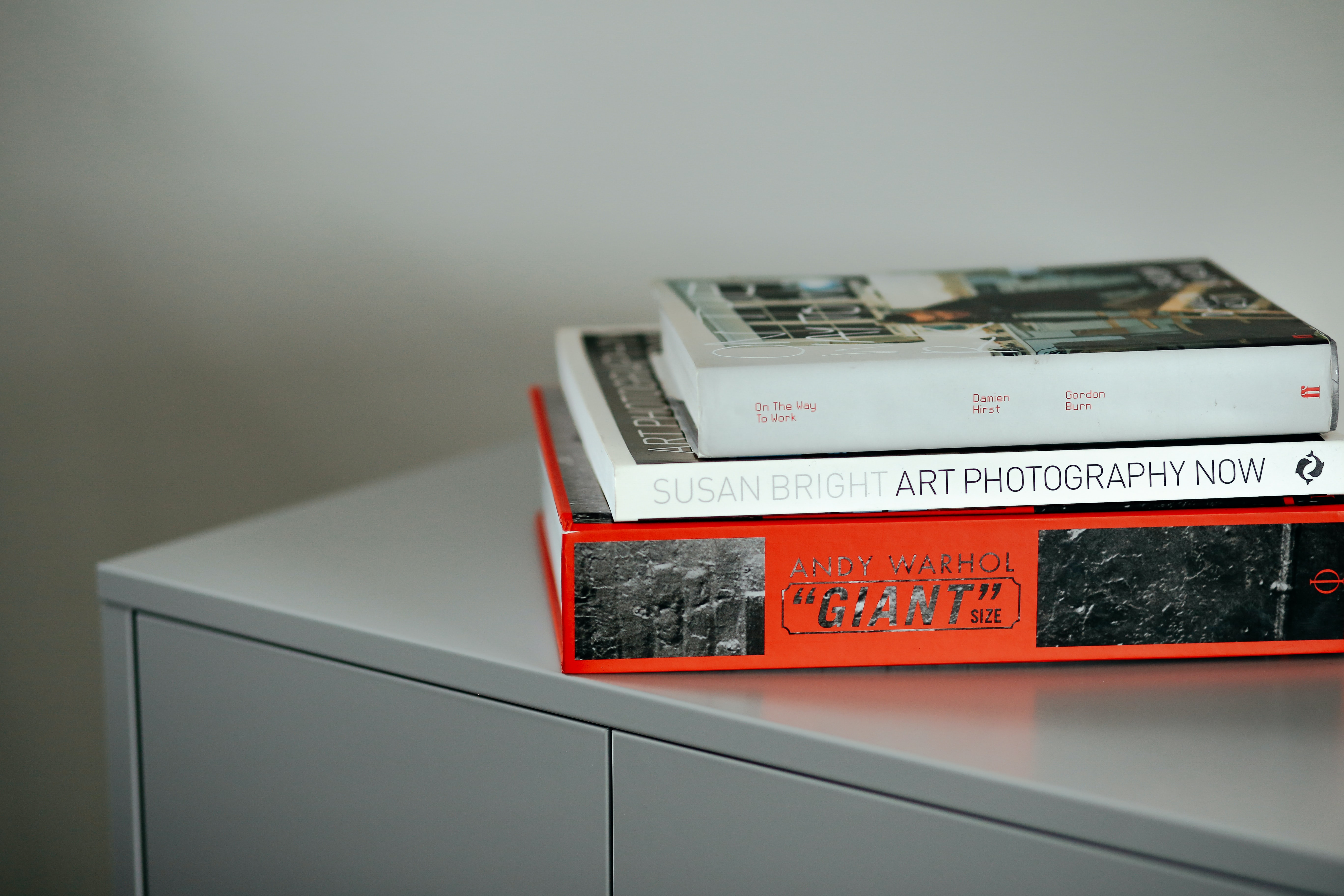 Three art books stacked on a metal cabinet