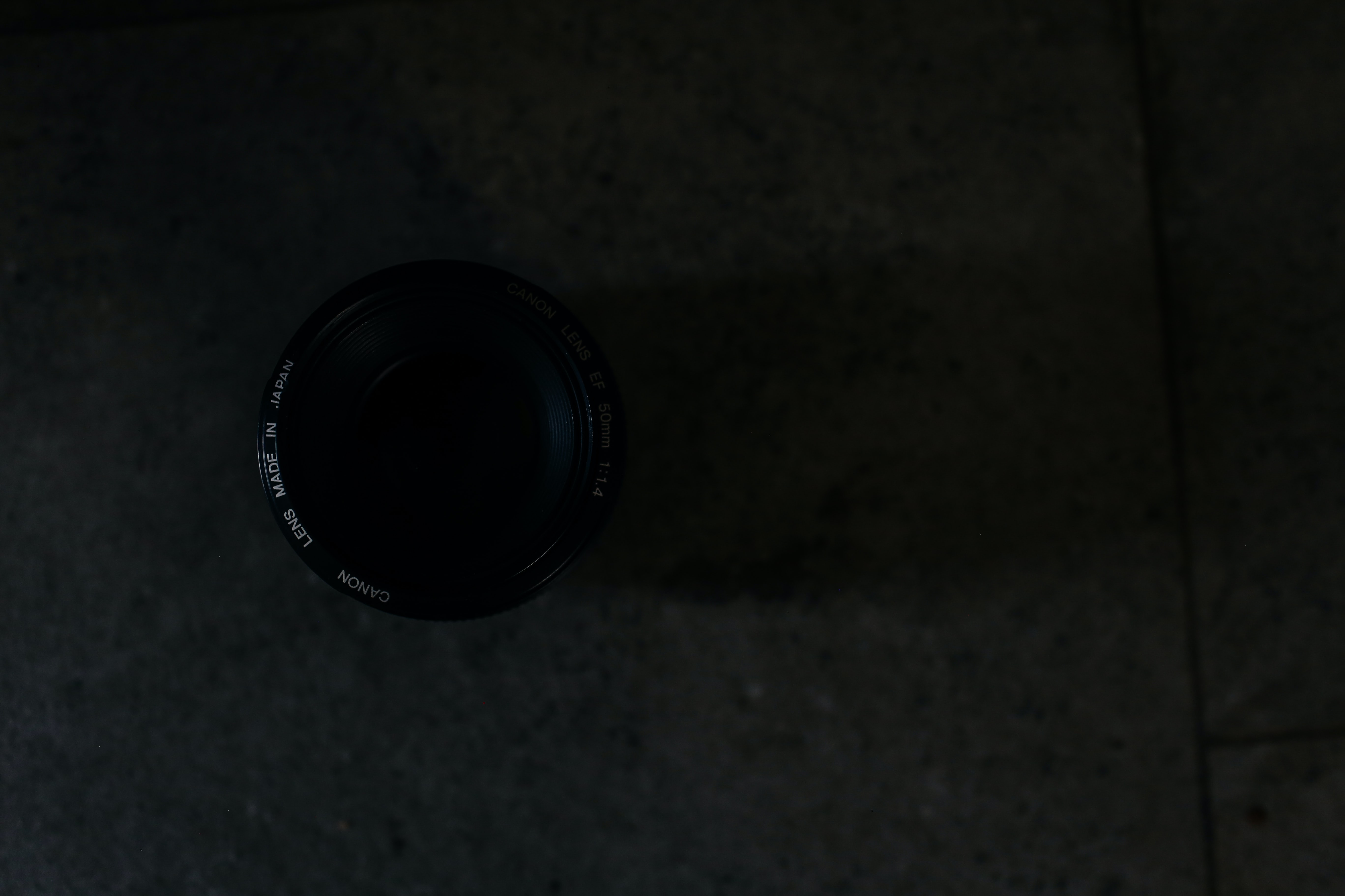 A canon lens resting on a stone floor at night