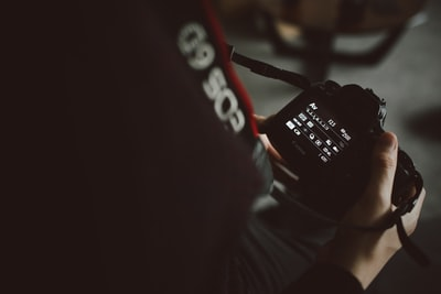 person holding black dslr camera canon teams background