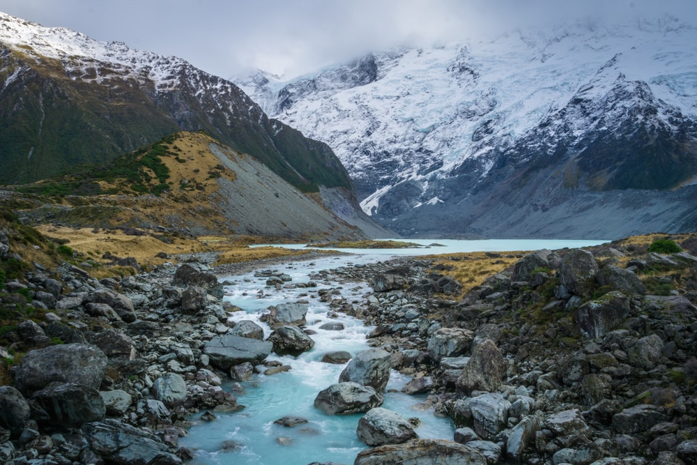 river with gray rocks near mountain covered in snow