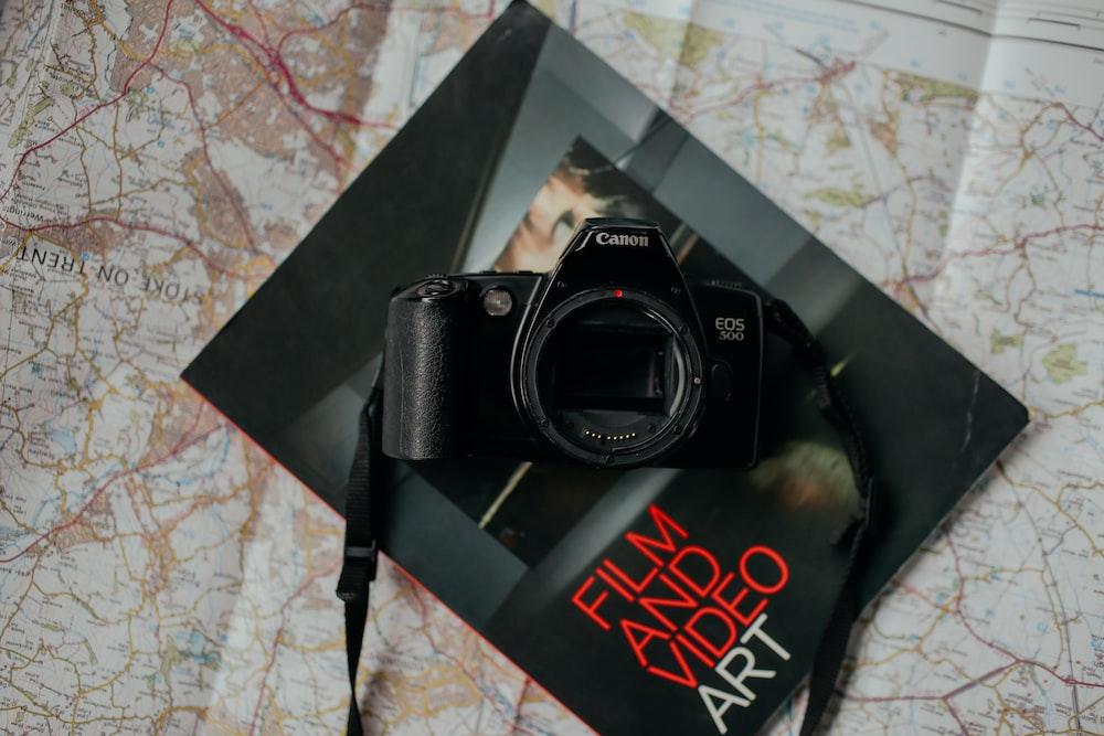 black Canon DSLR camera on top of black book