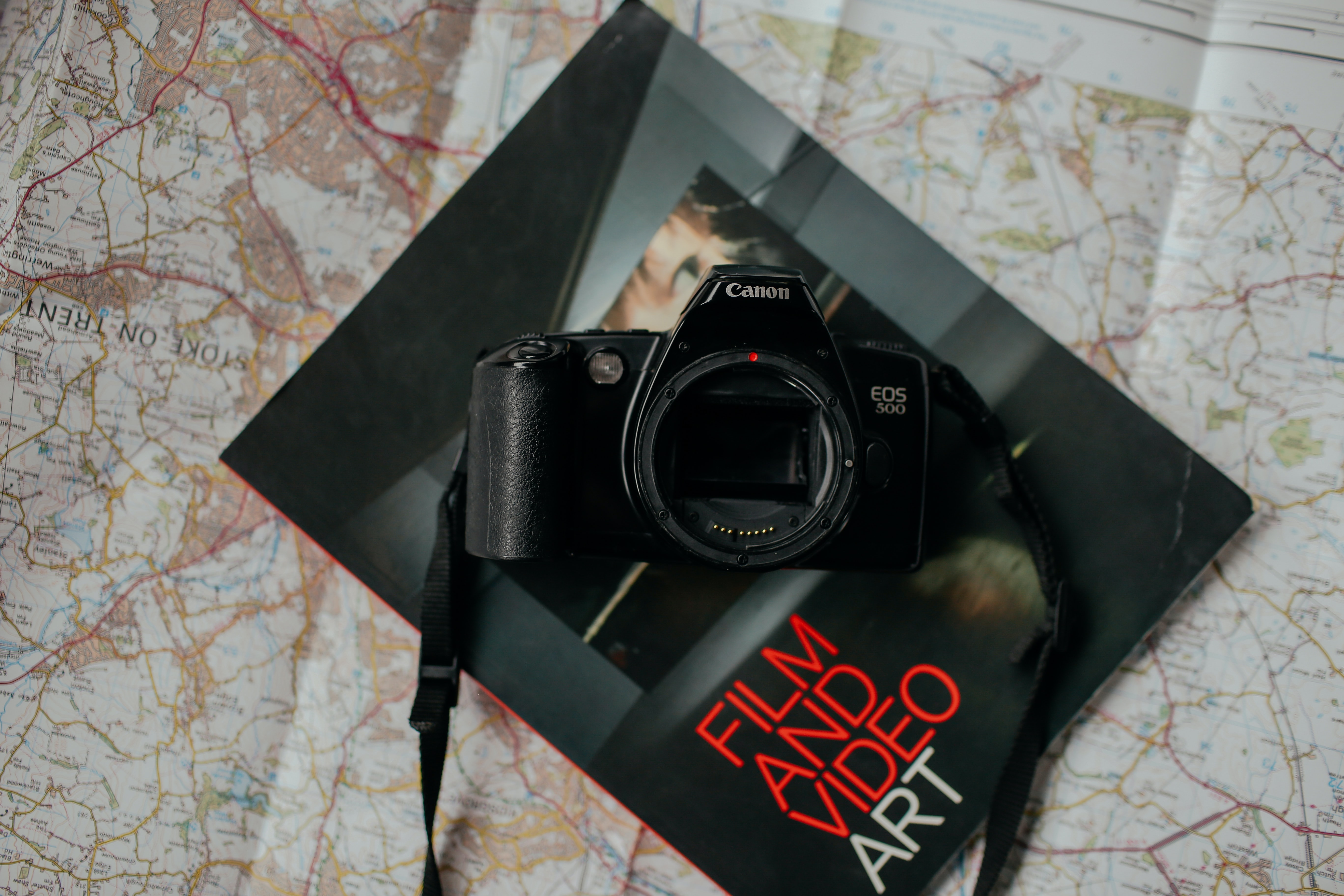 Canon EOS 500 camera without a lens on a Film and Video Art magazine on top of a map of Stoke on Trent