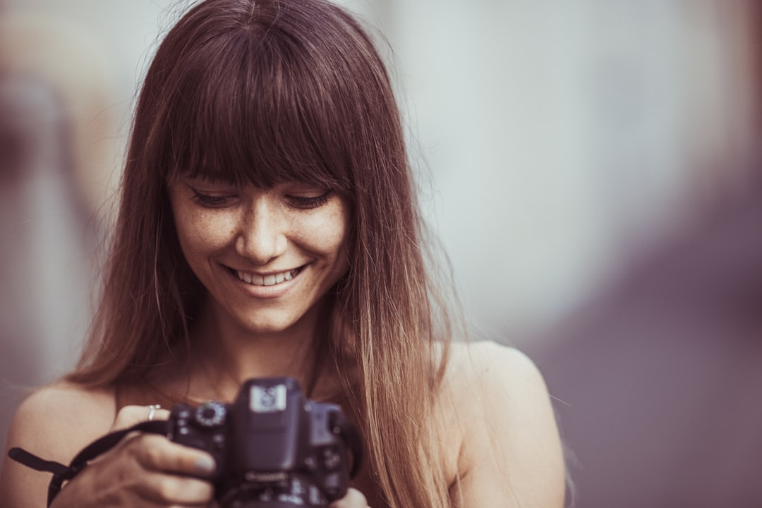 A woman with brown hair and bangs smiles town toward her camera against a blurry background