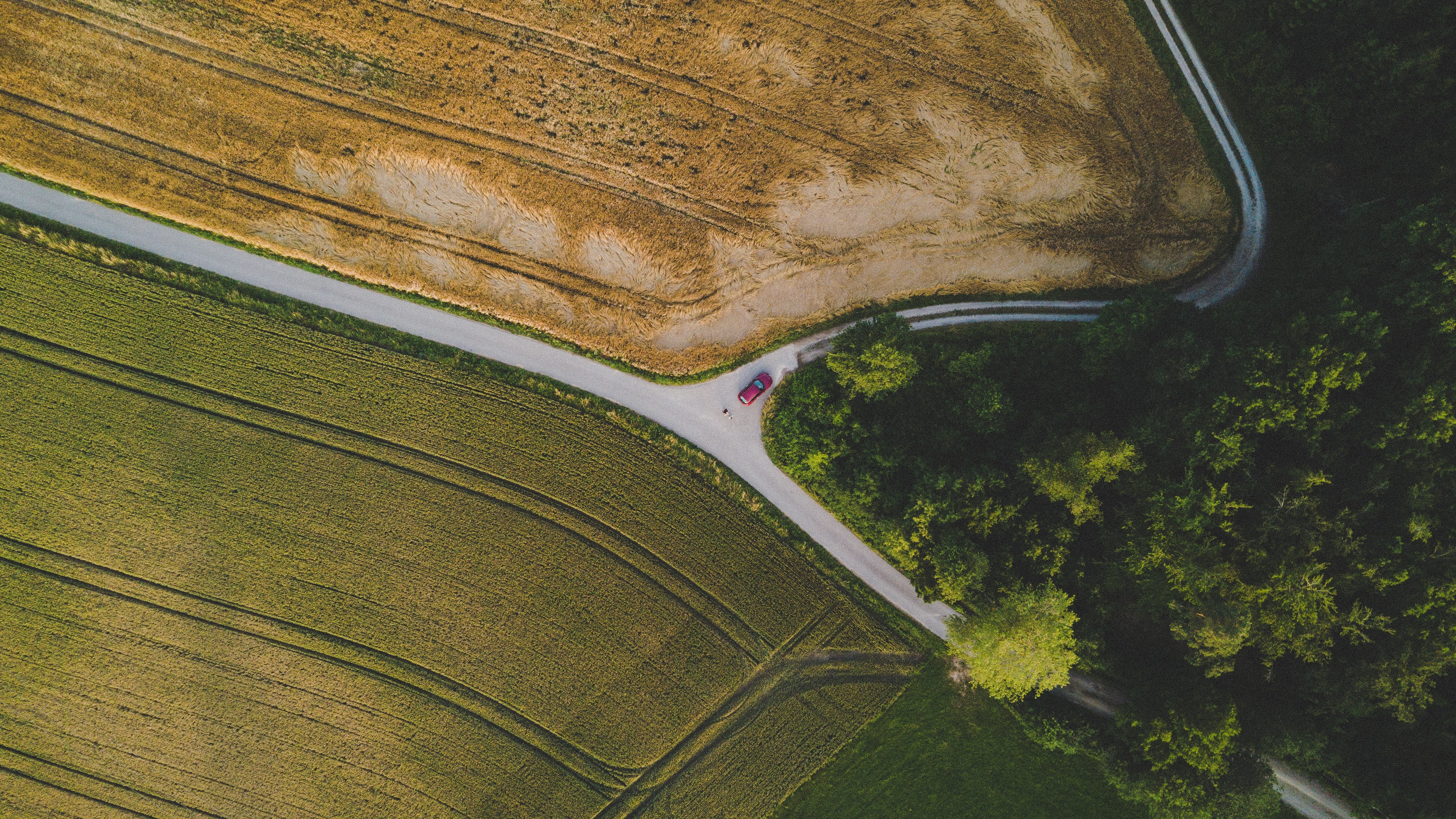 A drone shot of a car at a rural intersection surrounded by fields