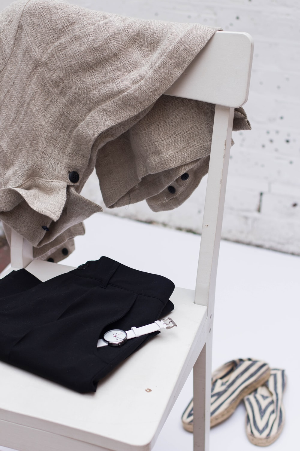 Clothes and a watch on a white wooden chair
