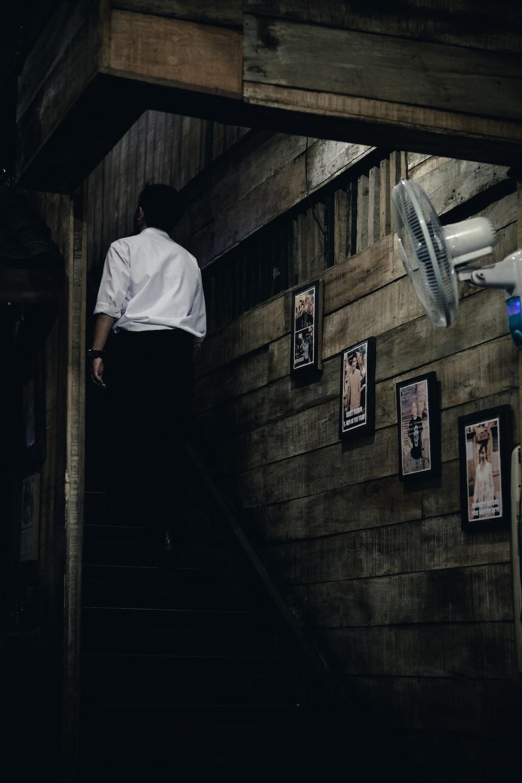 man in white dress shirt and black dress pants walking upstairs inside brown house