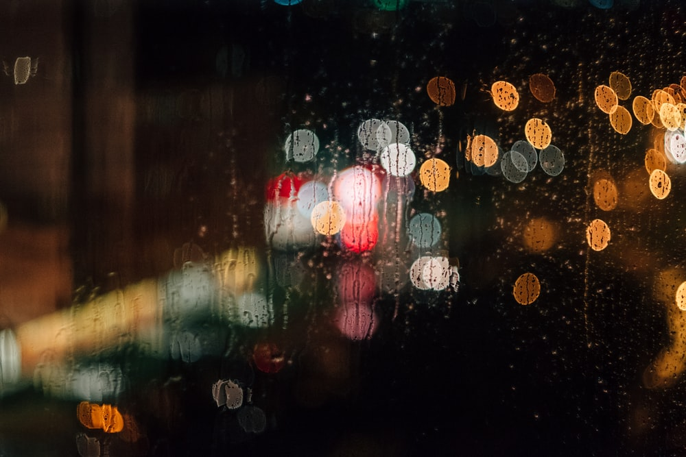 A rain-streaked window with a bokeh effect