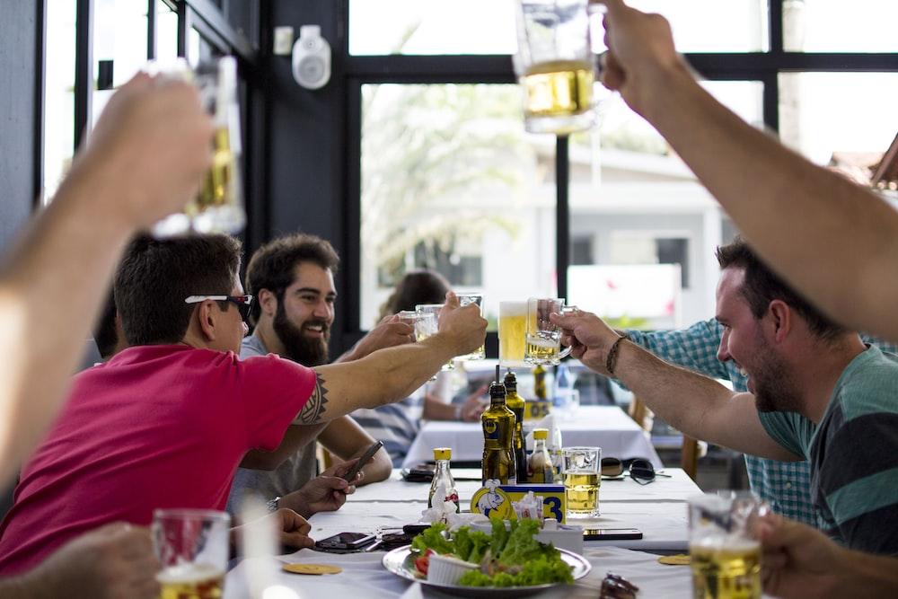 men doing toast beside table