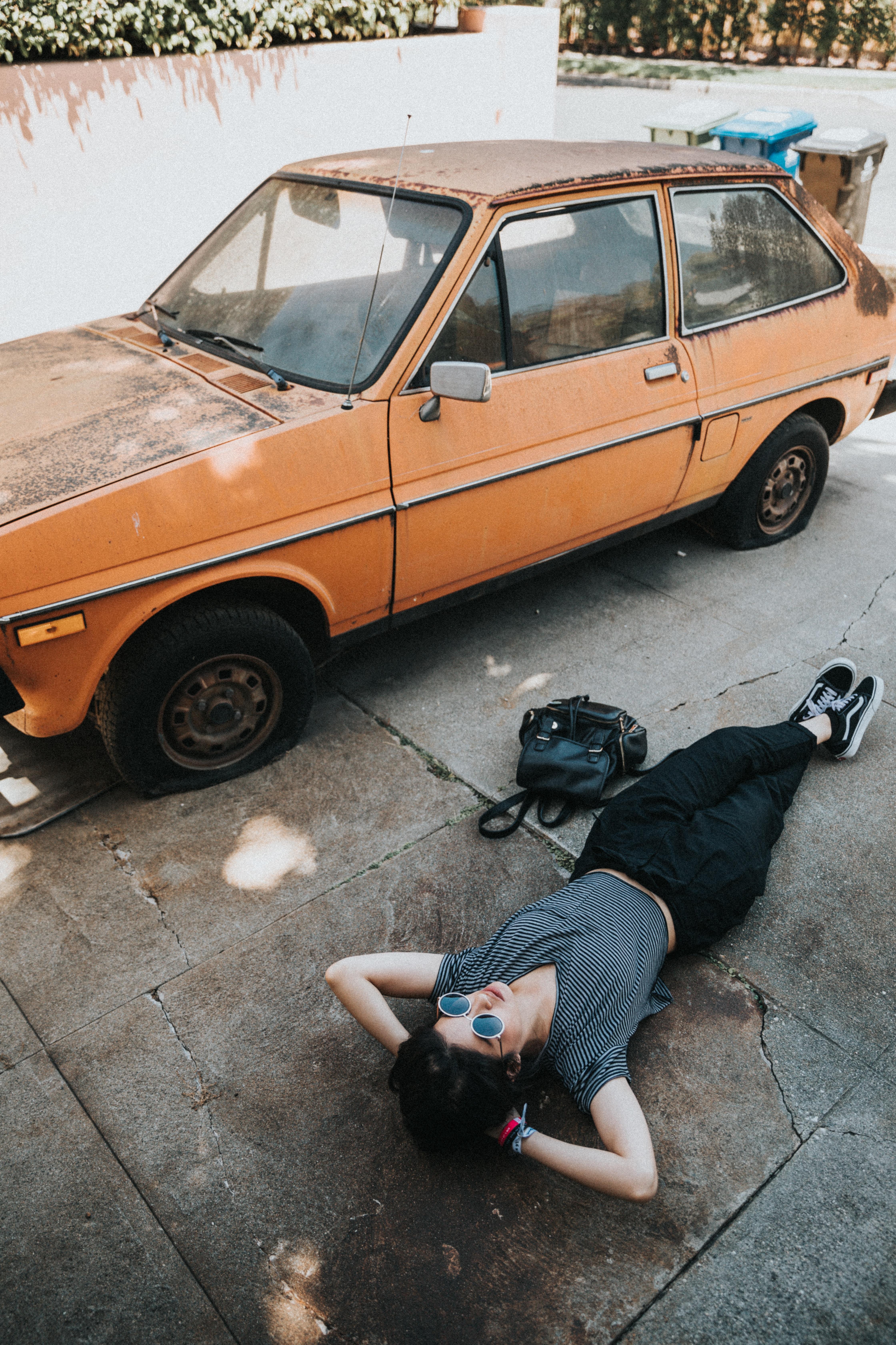 A woman lying down next to an old orange car.