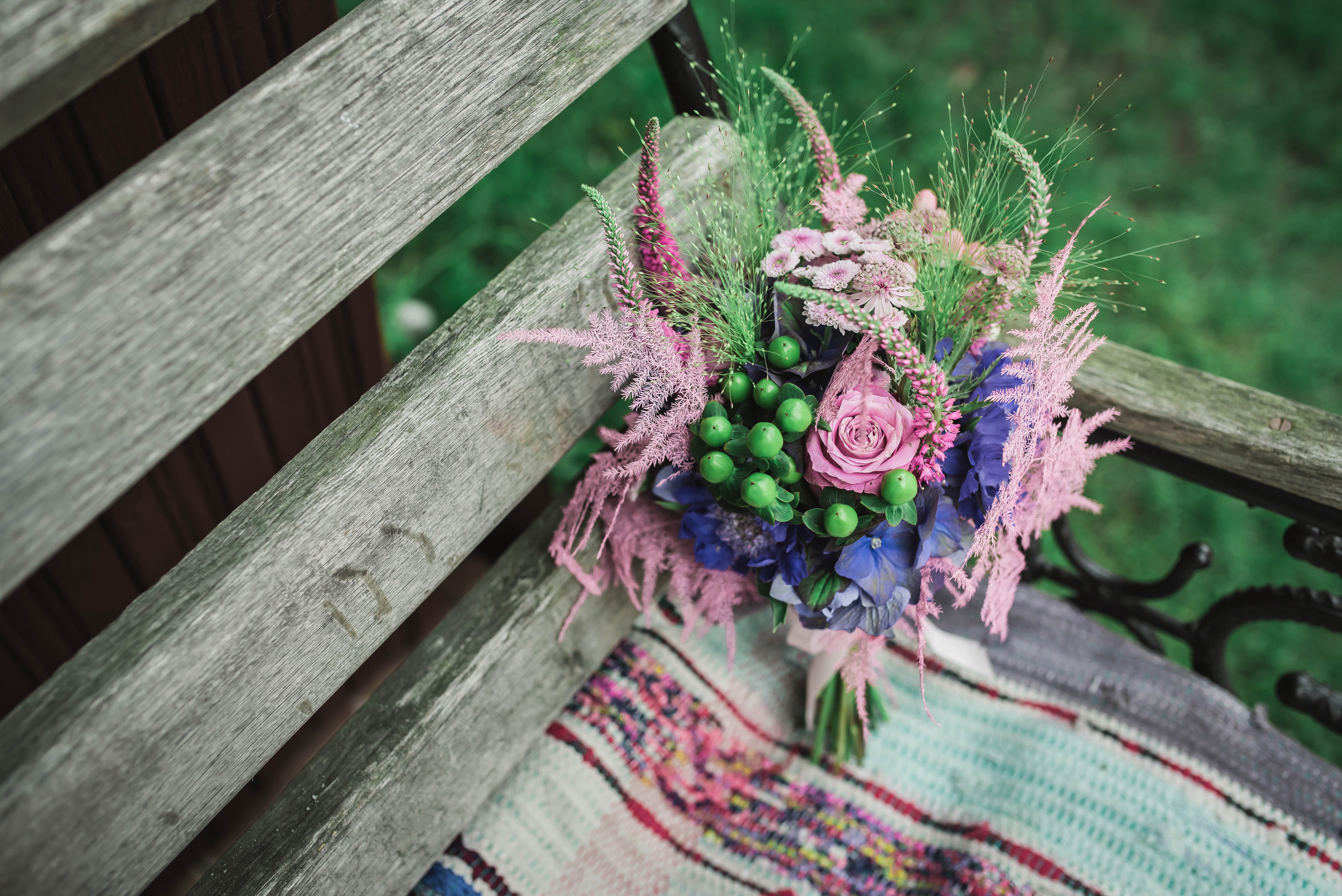 A bouquet of various flowers, berries and grasses on an old wooden bench