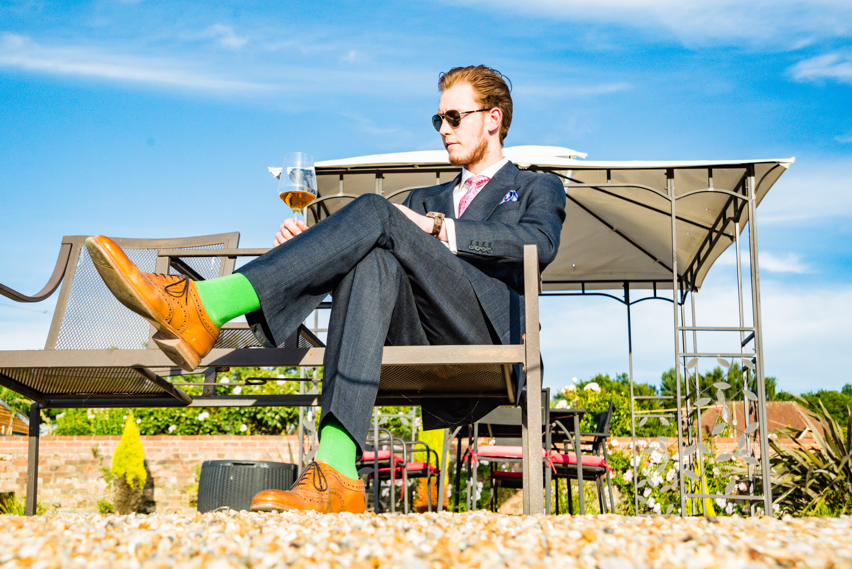 man wearing formal suit sitting near gazebo and green plants during daytime