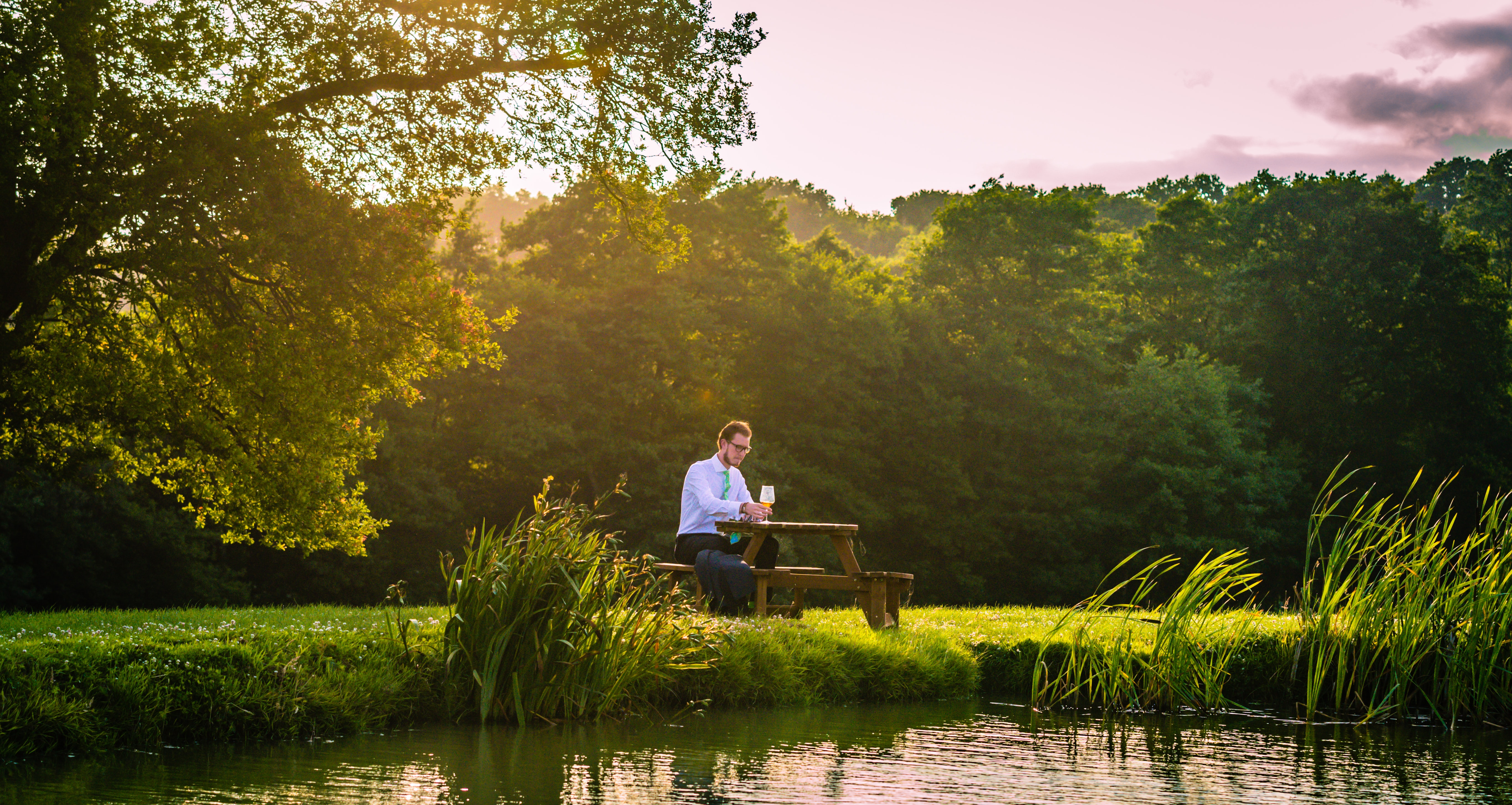 A dressed-up man sits alone, drinking wine at a picnic table aside a lake and trees