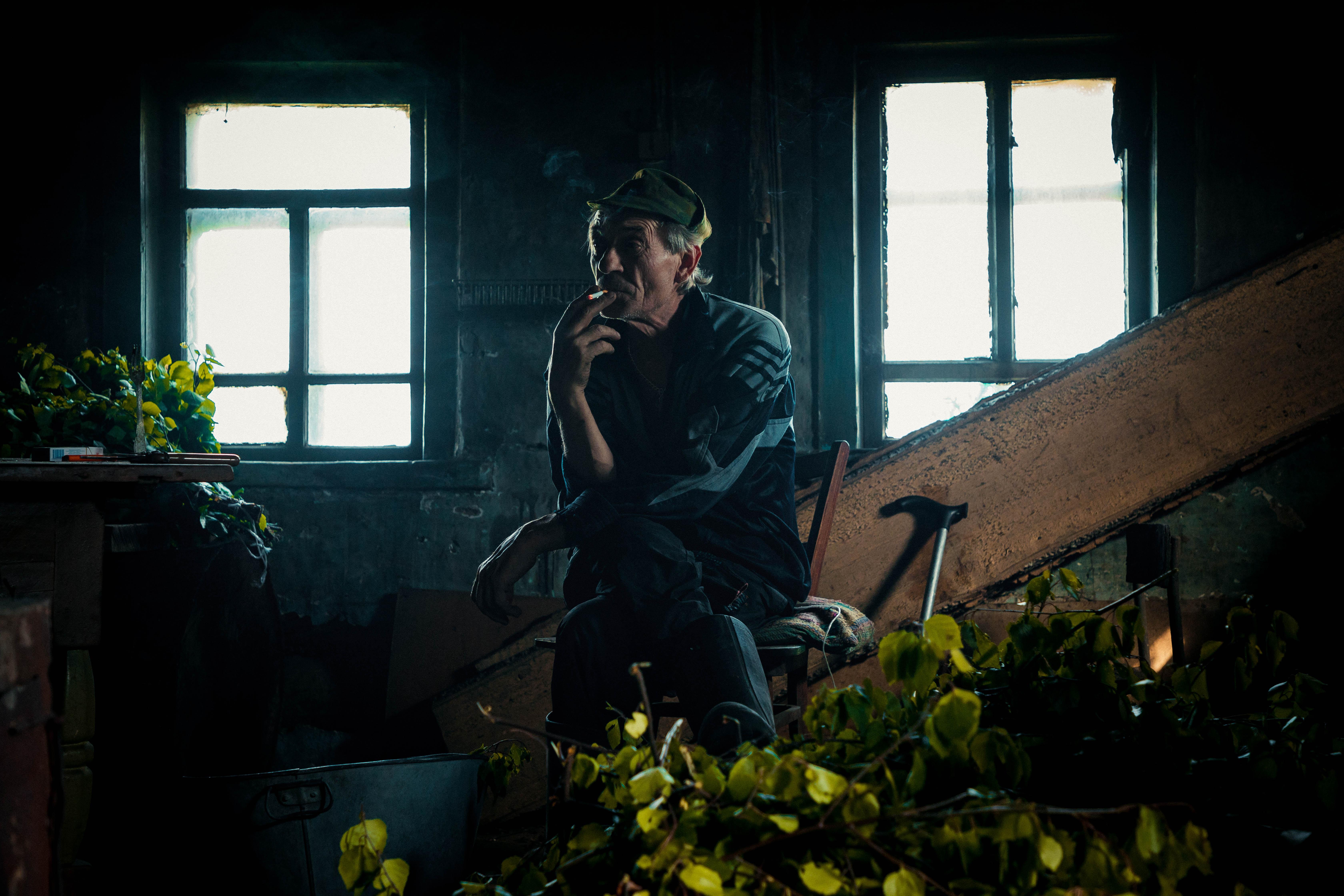 Older man sitting by the window in a dimly lit room smoking a cigarette in Knyazeva, Russia.