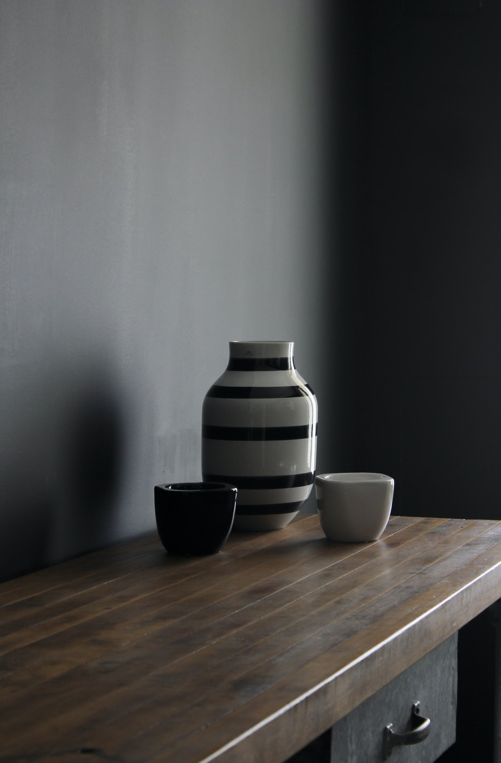 white and black striped ceramic vase on brown wooden table