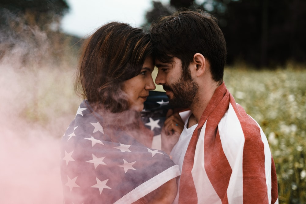 man standing in front of woman covered with U.S.A. flag