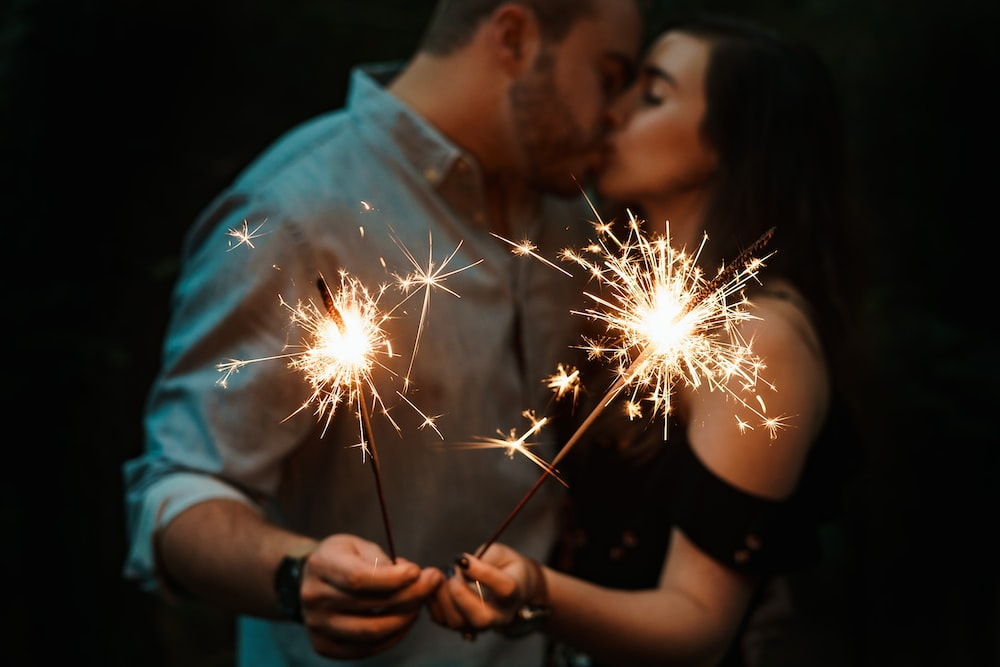 man and woman romantically kissing each other while holding fireworks, romance