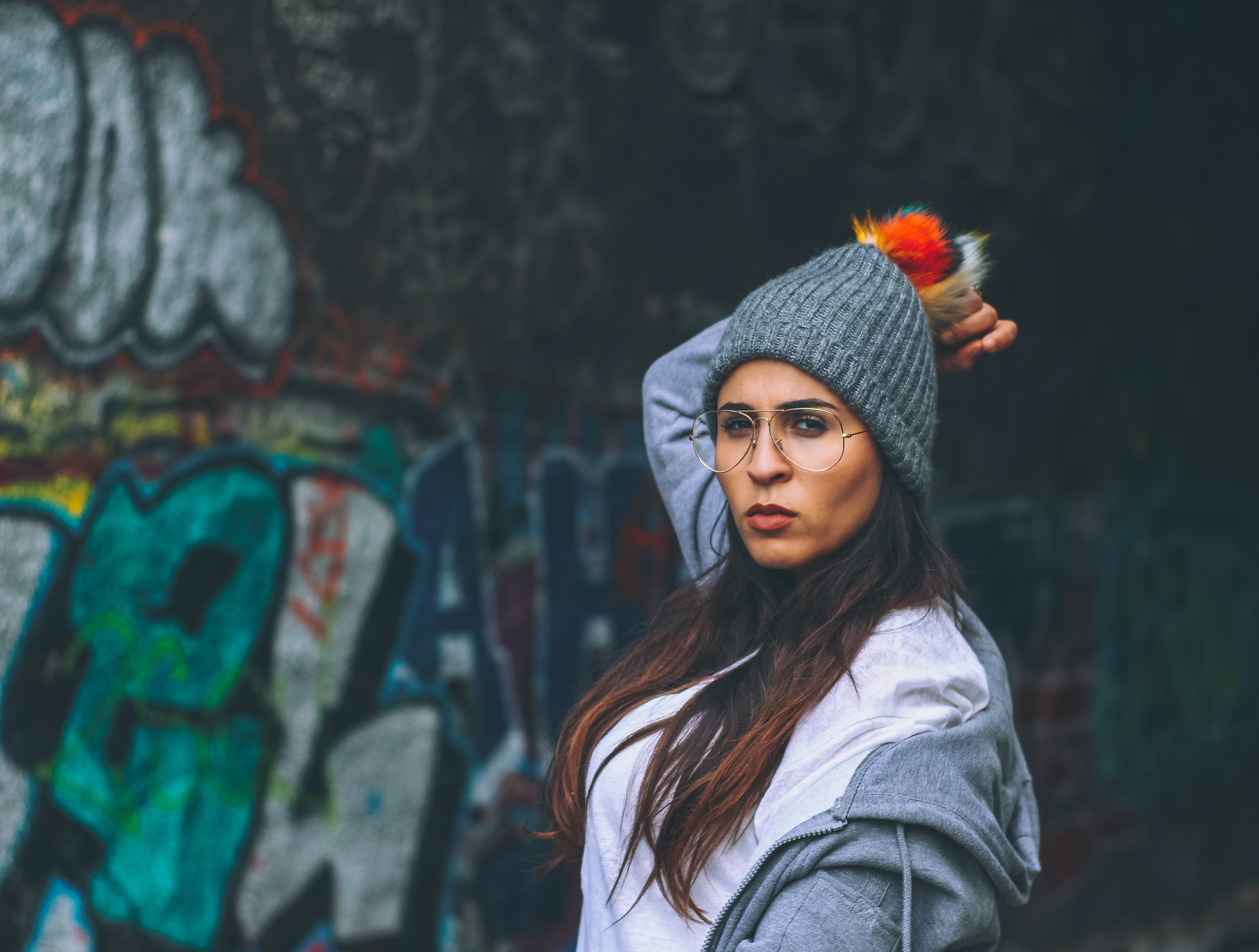 Attractive young fashion-conscious woman in grey bobble posing in front of urban wall with graffiti, Paris