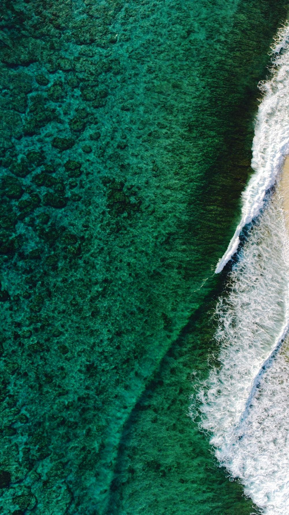 birds eye photography of wave of water on seashore