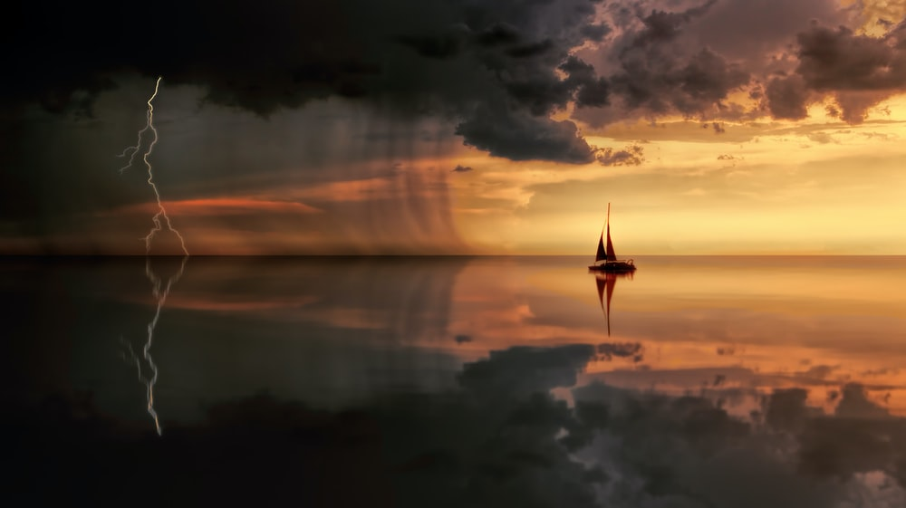A sailboat in the ocean during a lightning storm.