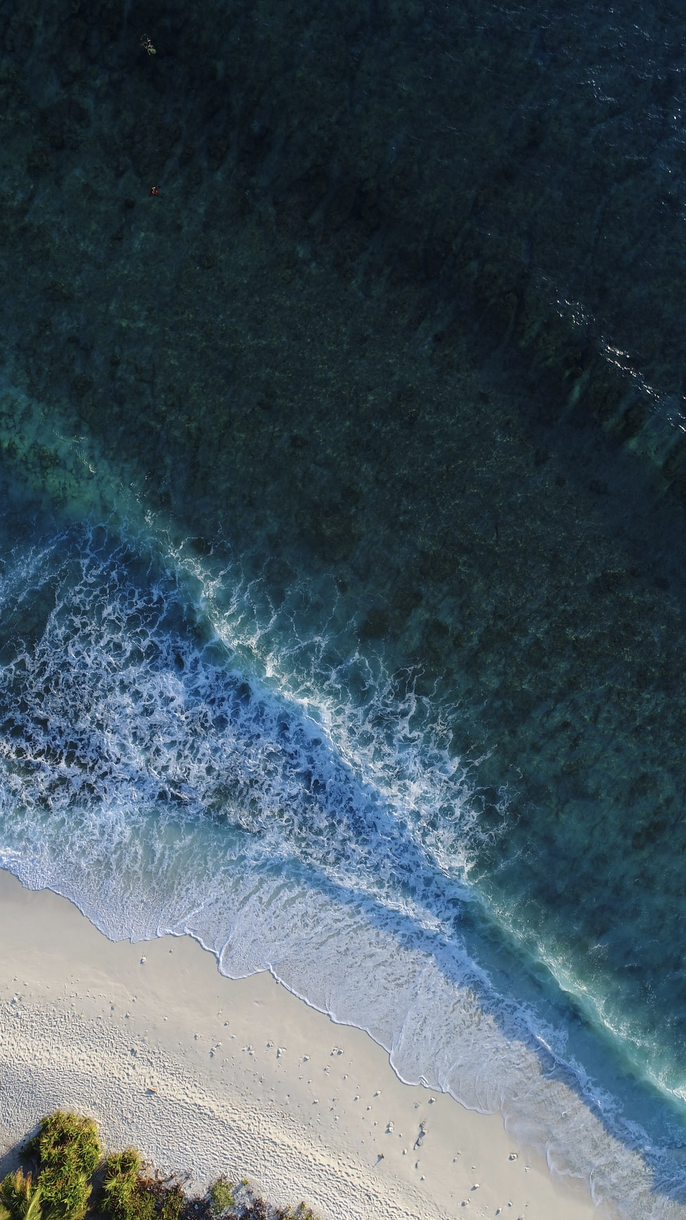 turquoise calm sea wave splashing on white sand beach aerial photography