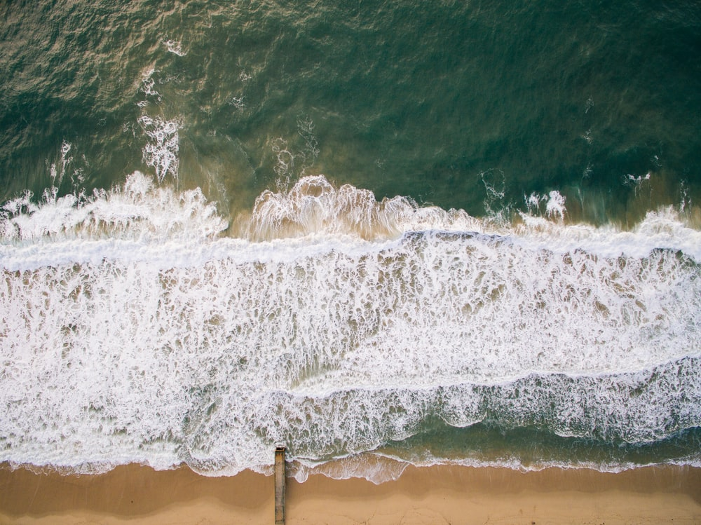 top view photography of brown beach sand with teal ocean water during daytime
