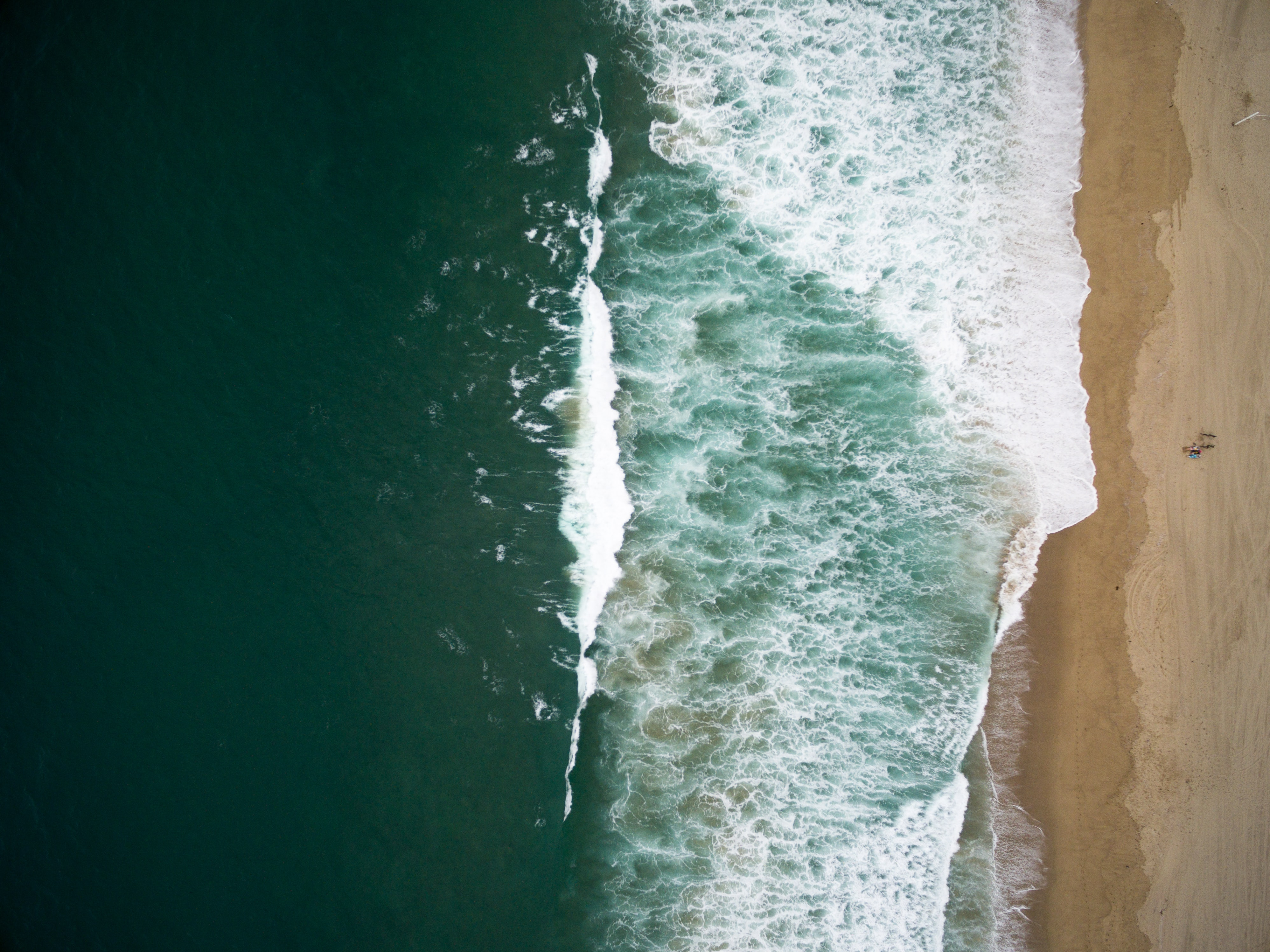 Drone aerial view of the ocean washing on the sand beach in South Redondo, Redondo Beach, California,