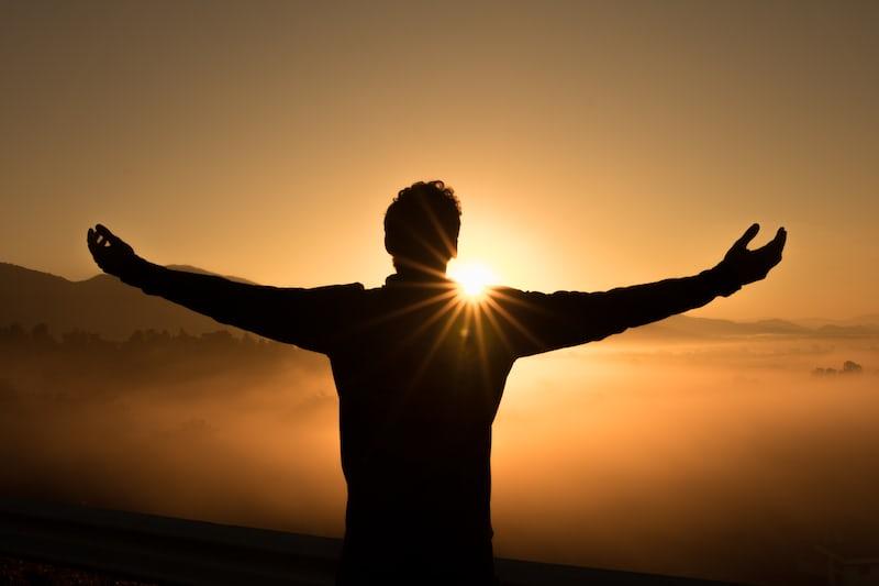 太陽を仰ぐ男性のシルエット